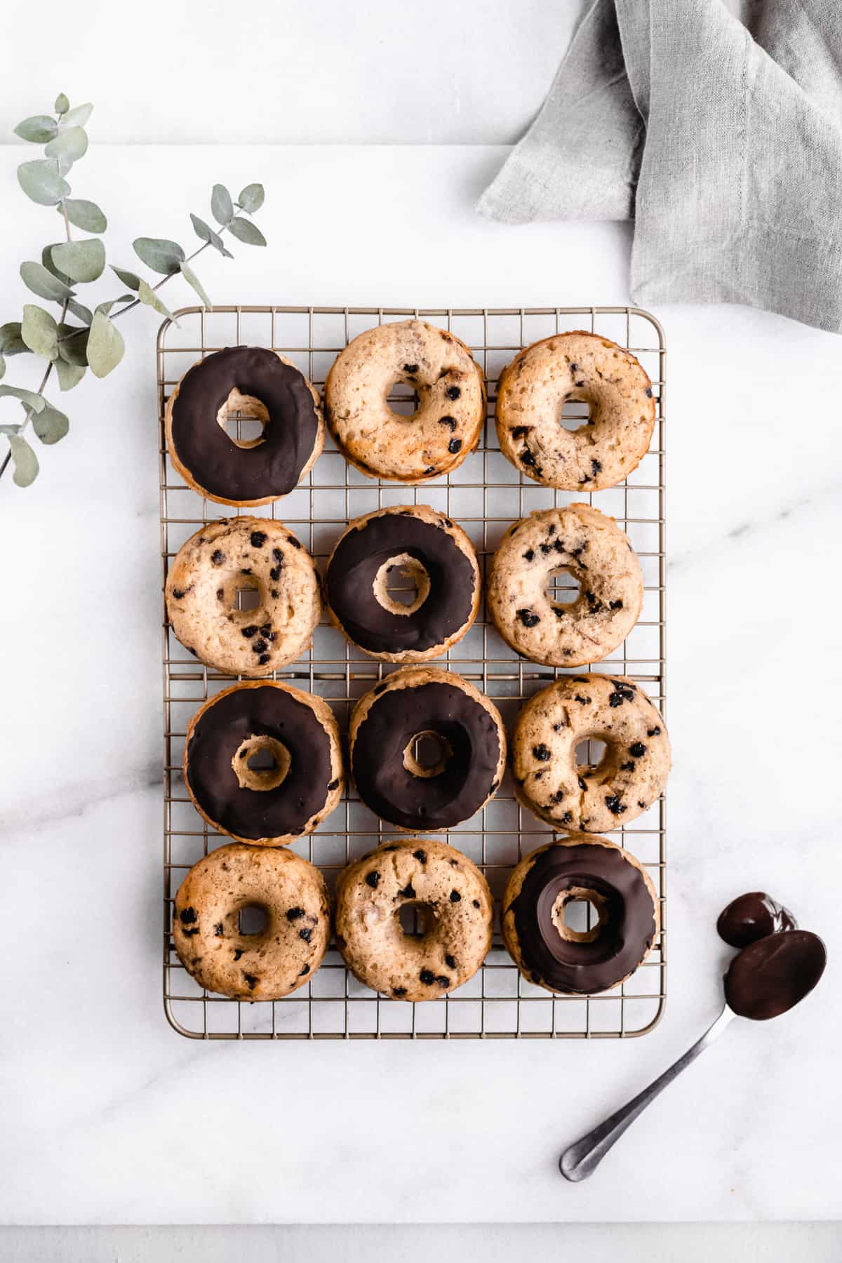 Overhead image of twelve Banana Bread Doughnuts laying on a cooling rack on a white marble slab.  Several of them have been frosted with chocolate icing.