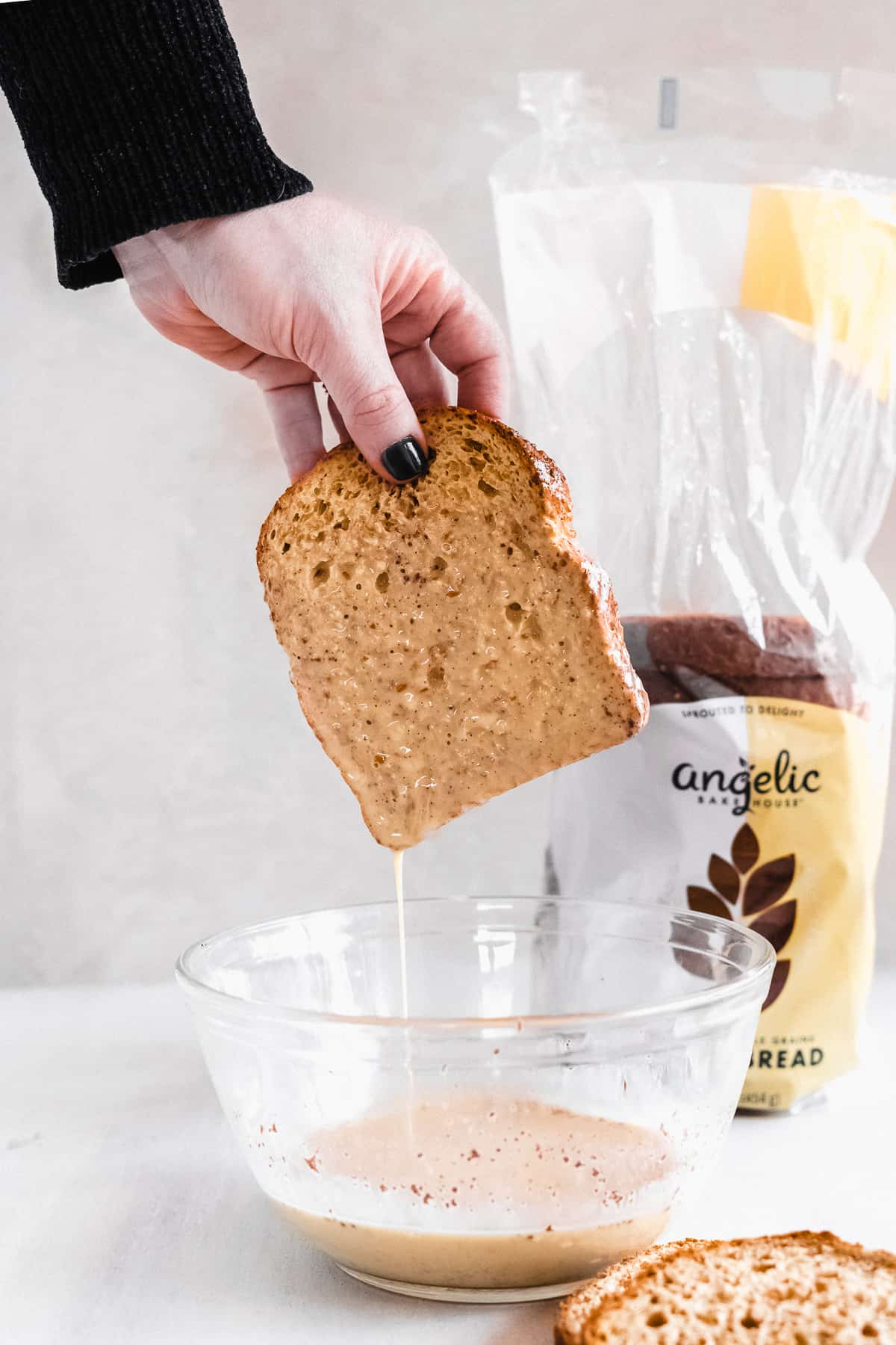 Side view image of a hand holding a slice of bread after being dunked into a bowl below.
