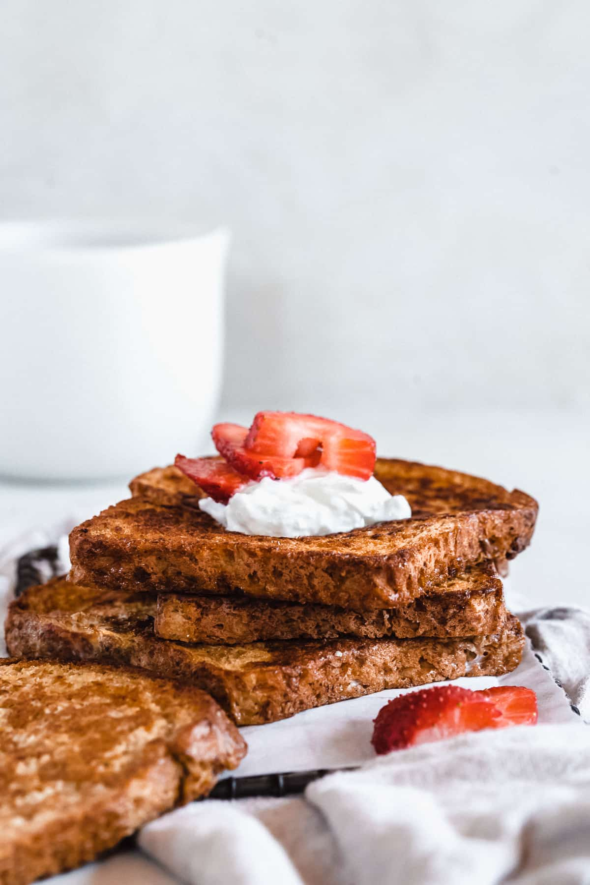 Side view image of three slices of French Toast stacked on top of one another.  A dollop of whipped cream and sliced strawberries are on top.