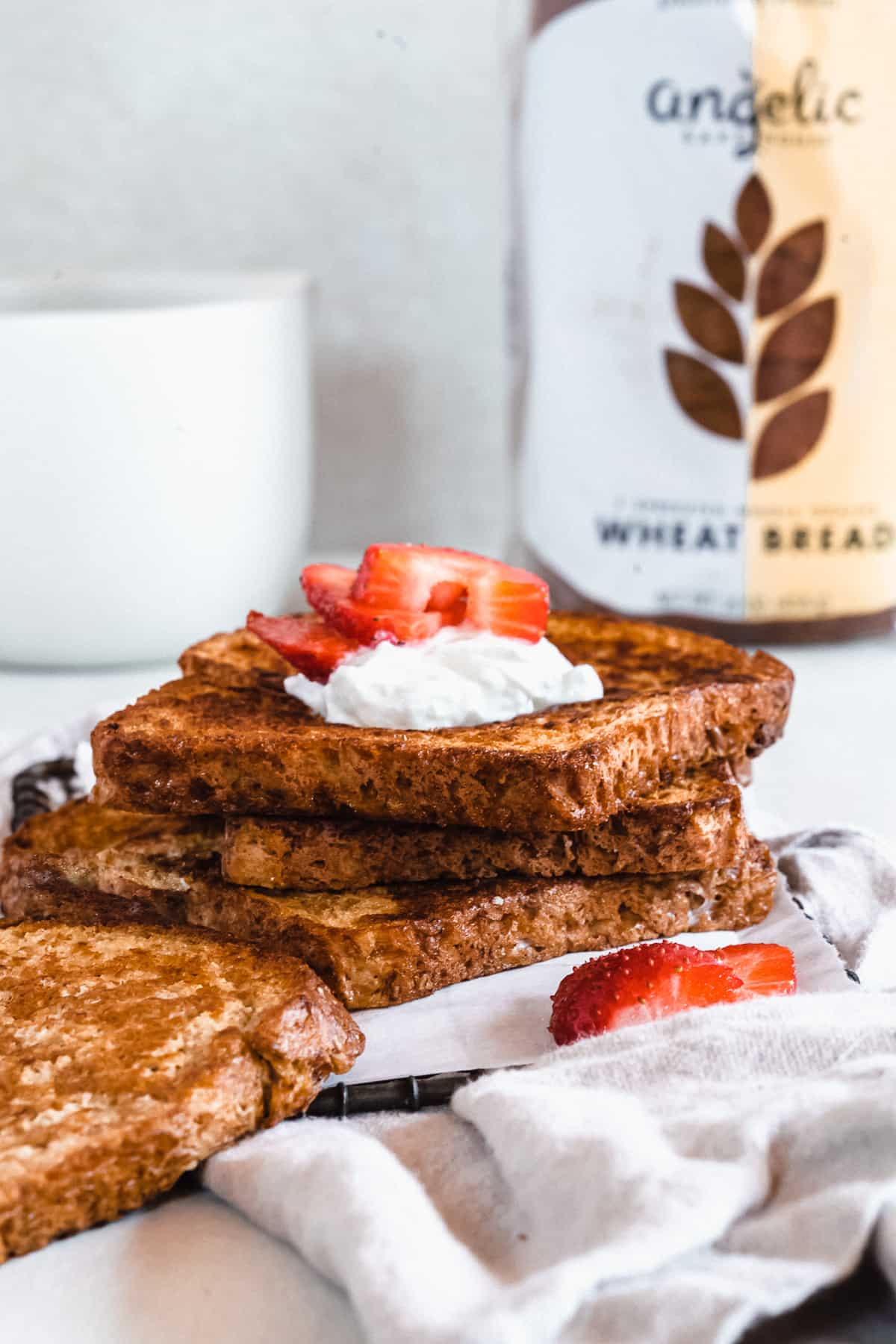 Side view image of three slices of French Toast stacked on parchment paper with a grey linen cloth underneath.  A coffee cup and loaf of Angelic Bakehouse bread is in the background.
