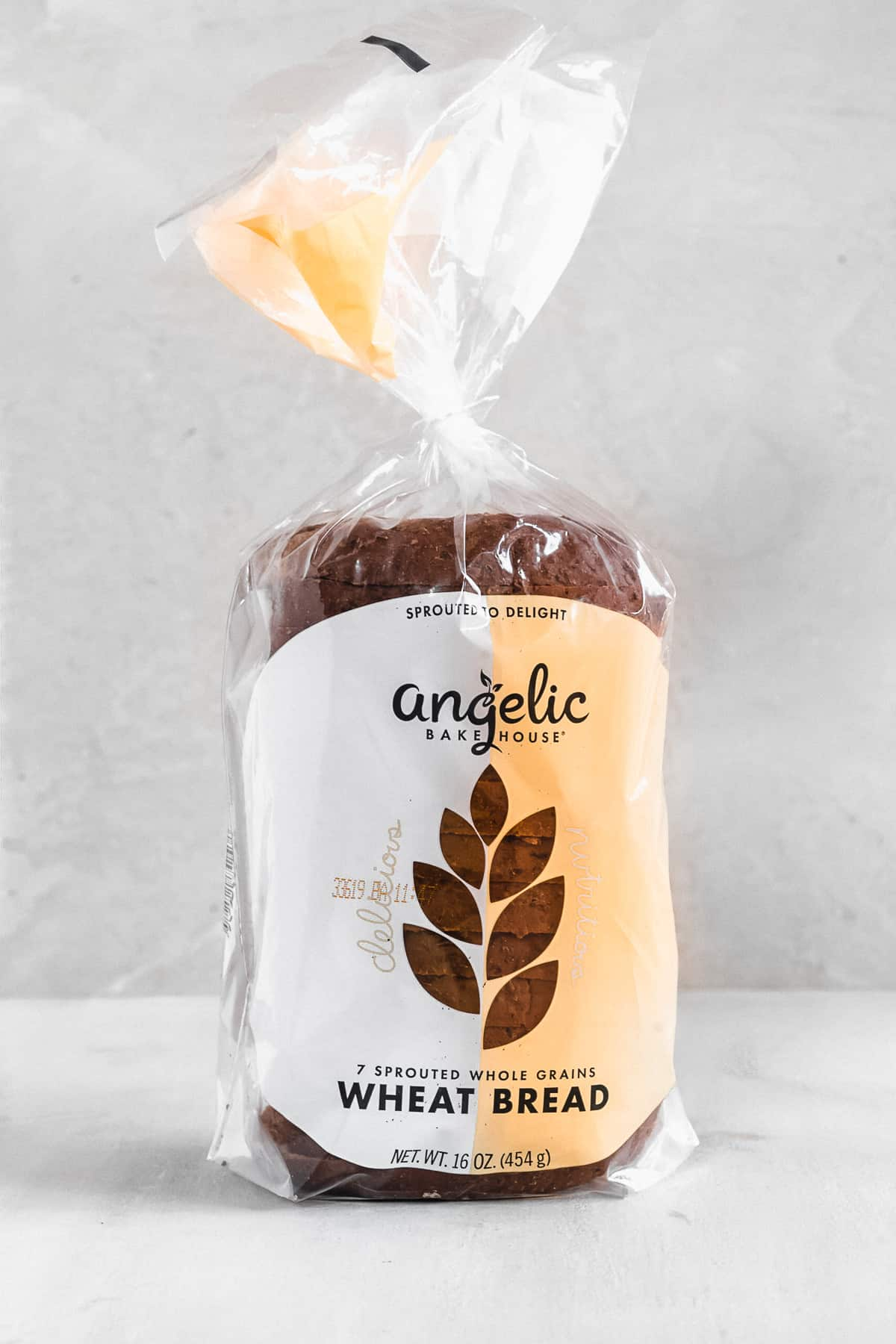 Side view photo of a loaf of Angelic Bakehouse Wheat Bread sitting on a white marble slab.