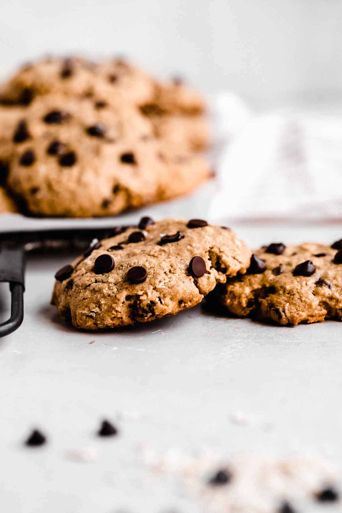 Side view image of two Oatmeal Chocolate Chip Cookies on a marble slab.  Additional cookies are on a cooling rack on the background.