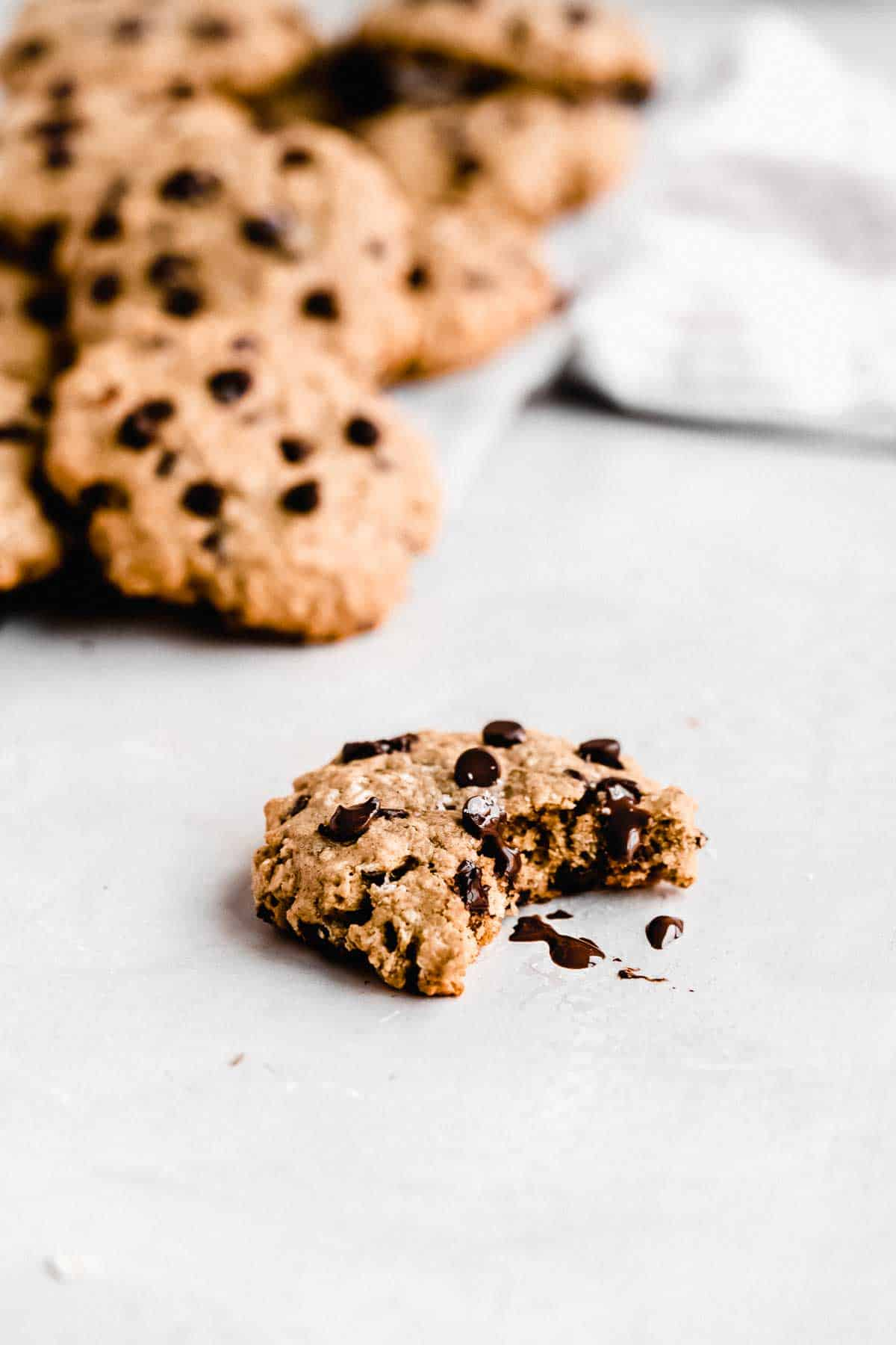 Close up image of a single Oatmeal Chocolate Chip Cookie with a bite taken out of it sitting on a marble slab.  Additional cookies are in the background.