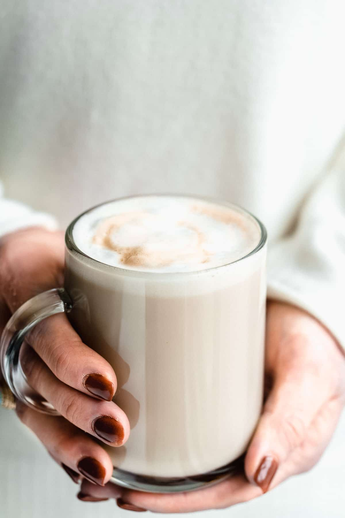 Side view image of two hands holding a clear mug of Maple Sea Salt Almond Milk Latte.