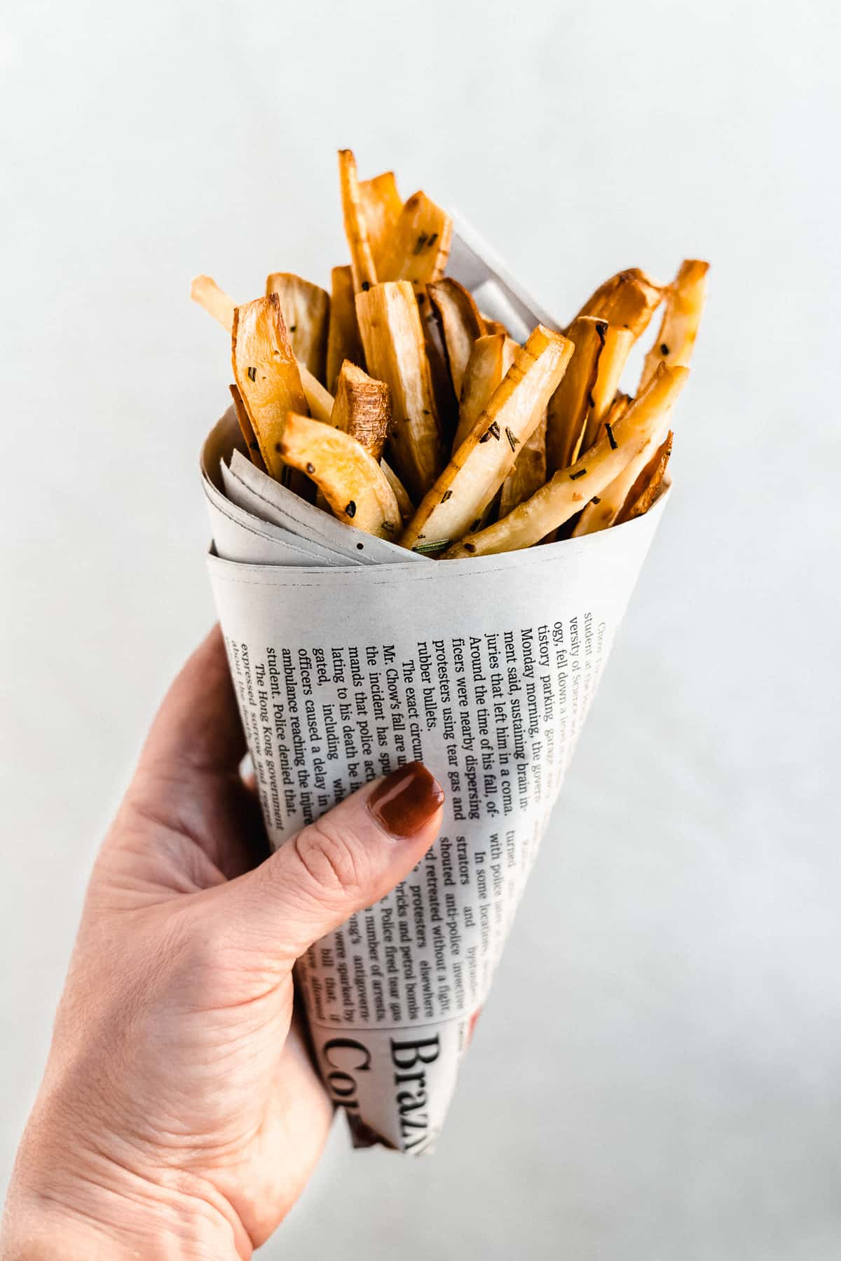 Side view image of Baked Parsnip Fries wrapped in a cone of newspaper being held up in the air by a hand.