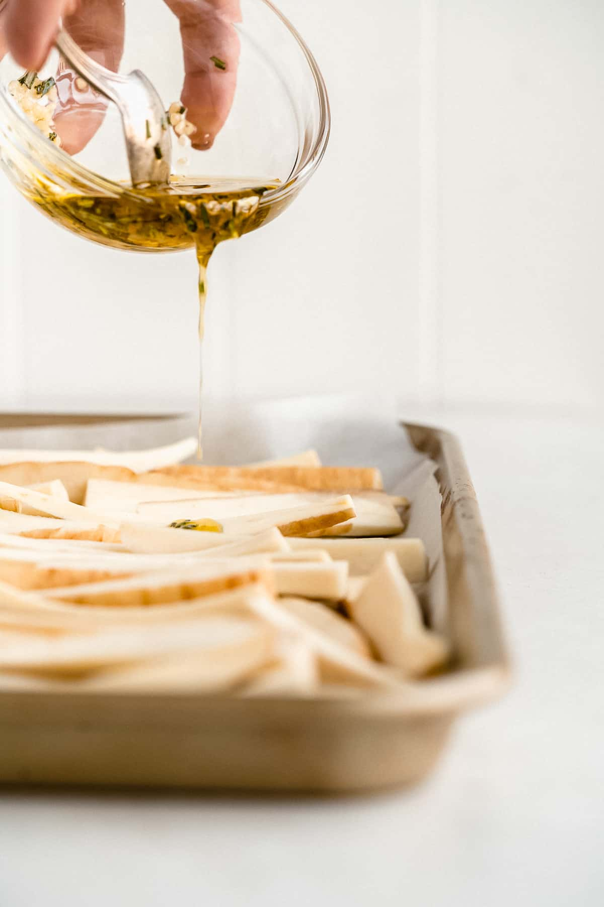Image of sliced parsnips arranged on parchment paper on a baking sheet.  A hand overhead is holding a small bowl of olive oil and spices and is drizzling the mixture over the parsnip slices below.