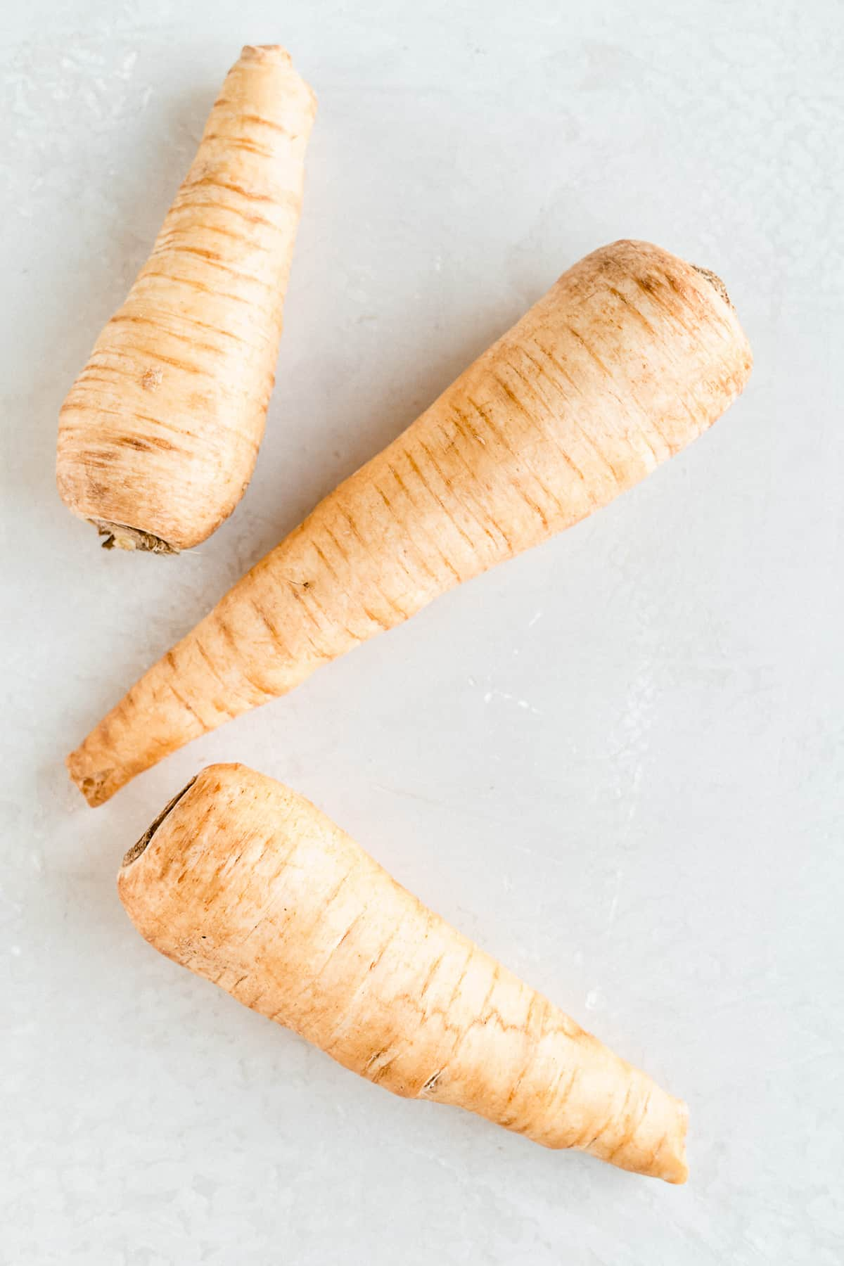 Overhead photo of several parsnips laying on a marble slab.