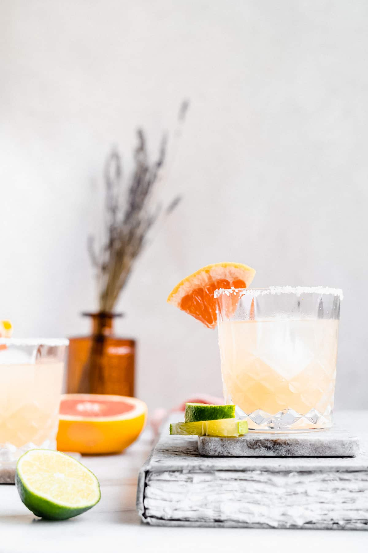 Side view photo of the Skinny Smoky Grapefruit Margarita served in a crystal glass that is sitting on a coaster on top of a book.  Half a grapefruit and a slice of lime are seen in the background.