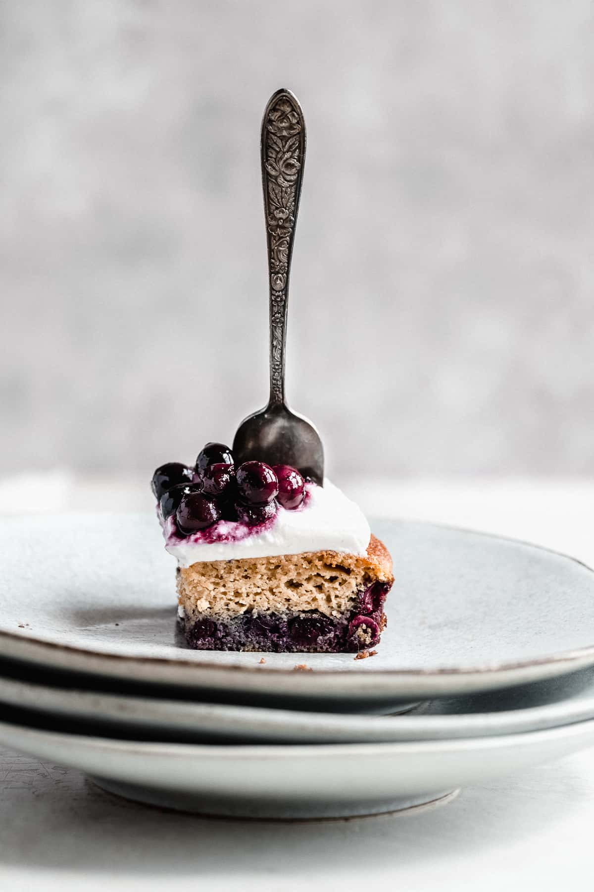 Side view photo of a single serving of Blueberry Vanilla Sheet Cake on a stack of gray plates with a silver fork sticking up from the cake.