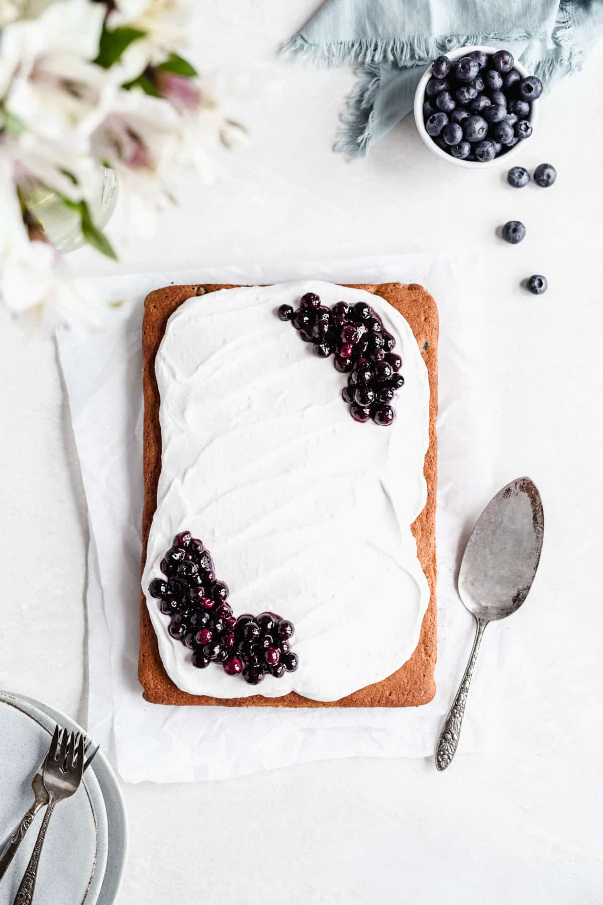 Overhead photo of completed Blueberry Vanilla Sheet Cake on a white marble slab.  A silver cake server is laying nearby.  Several small plates and forks can be seen in the background.  Additional blueberries are sprinkled around.