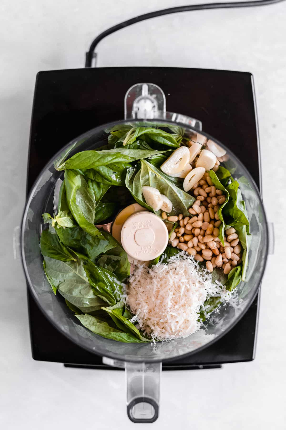 Overhead photo of the ingredients used in the basil pesto sauce layered in a food processor ready to be mixed.  Food processor is sitting on a white marble slab.