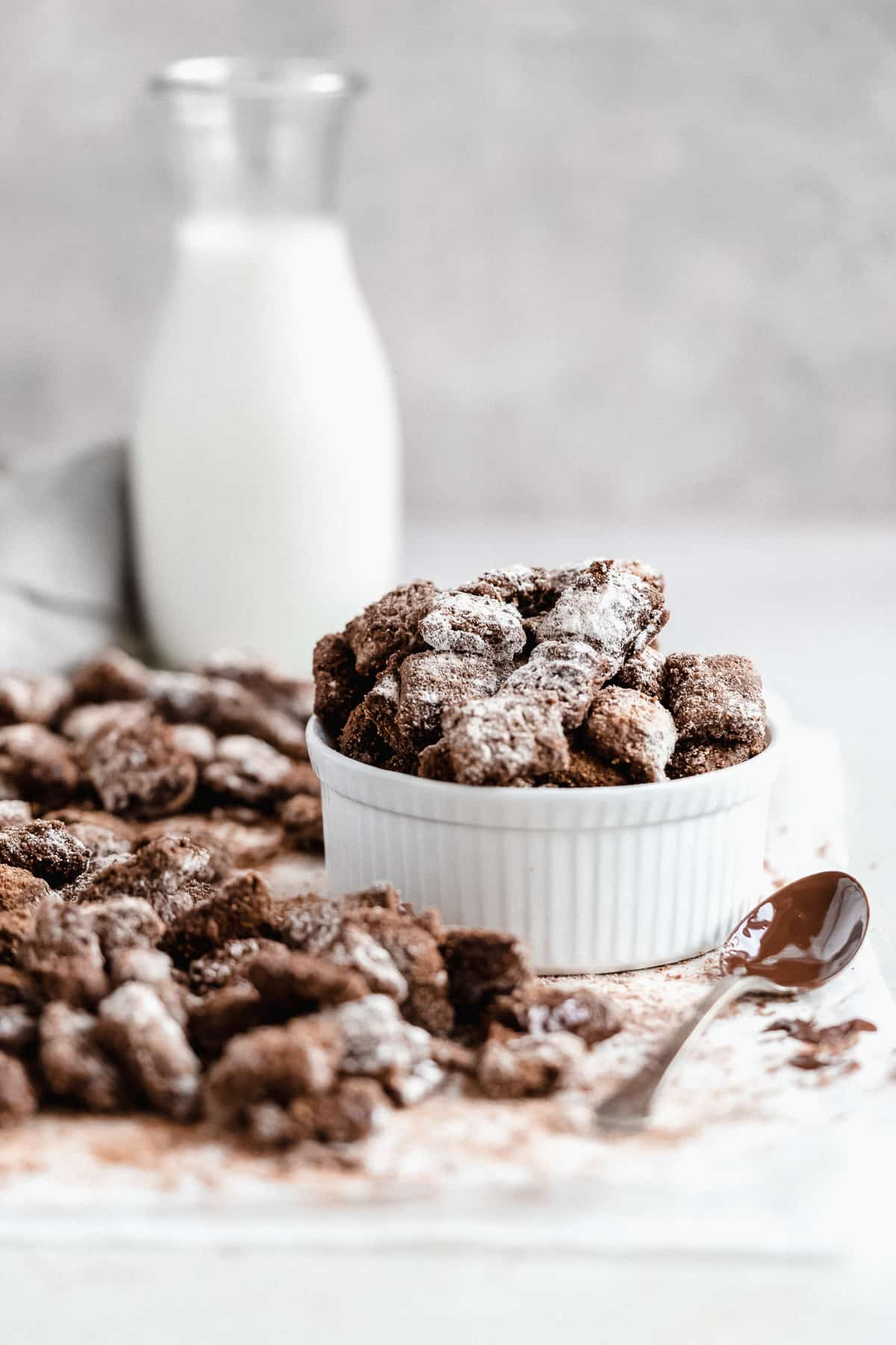 Side view photo of a white ramekin filled with Healthy Puppy Chow.  Additional Puppy Chow pieces are laying nearby.  A carafe of milk is in the background.