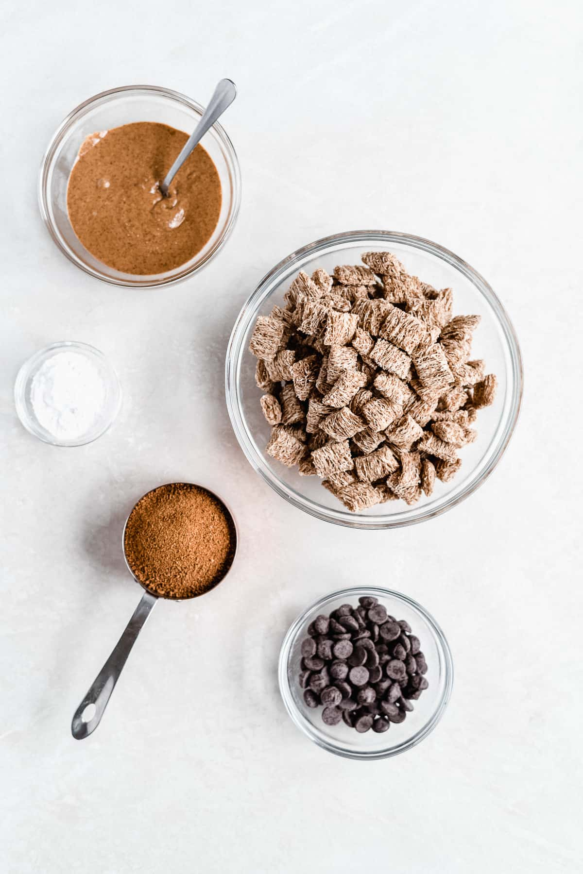 Overhead photo of the 5 ingredients needed to make Healthy Puppy Chow arranged on a white background.