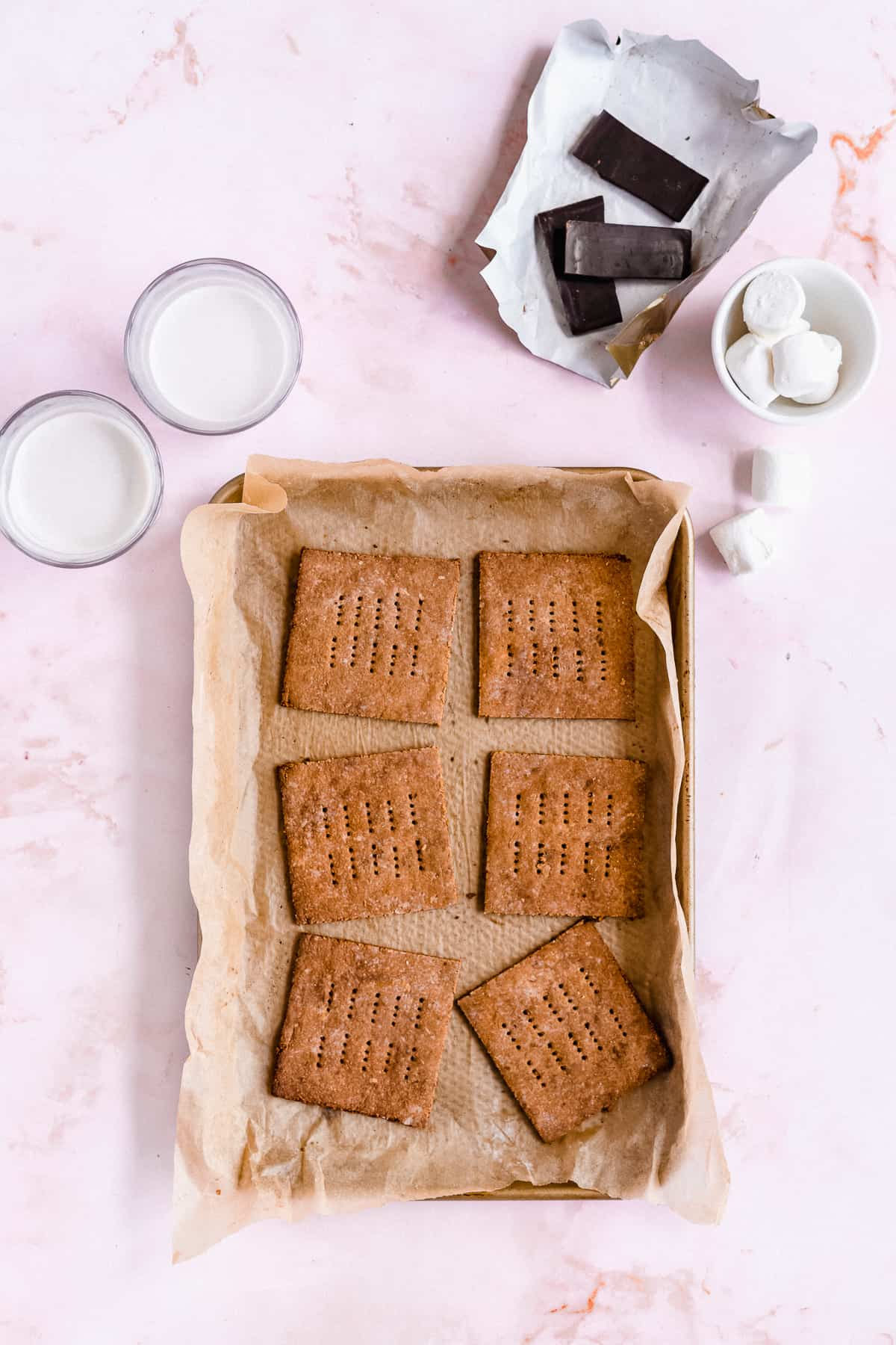 Overhead photo of freshly baked Homemade Graham Crackers on parchment paper on a baking sheet.  Two glasses of milk and some chocolate pieces and marshmallows are in the background.