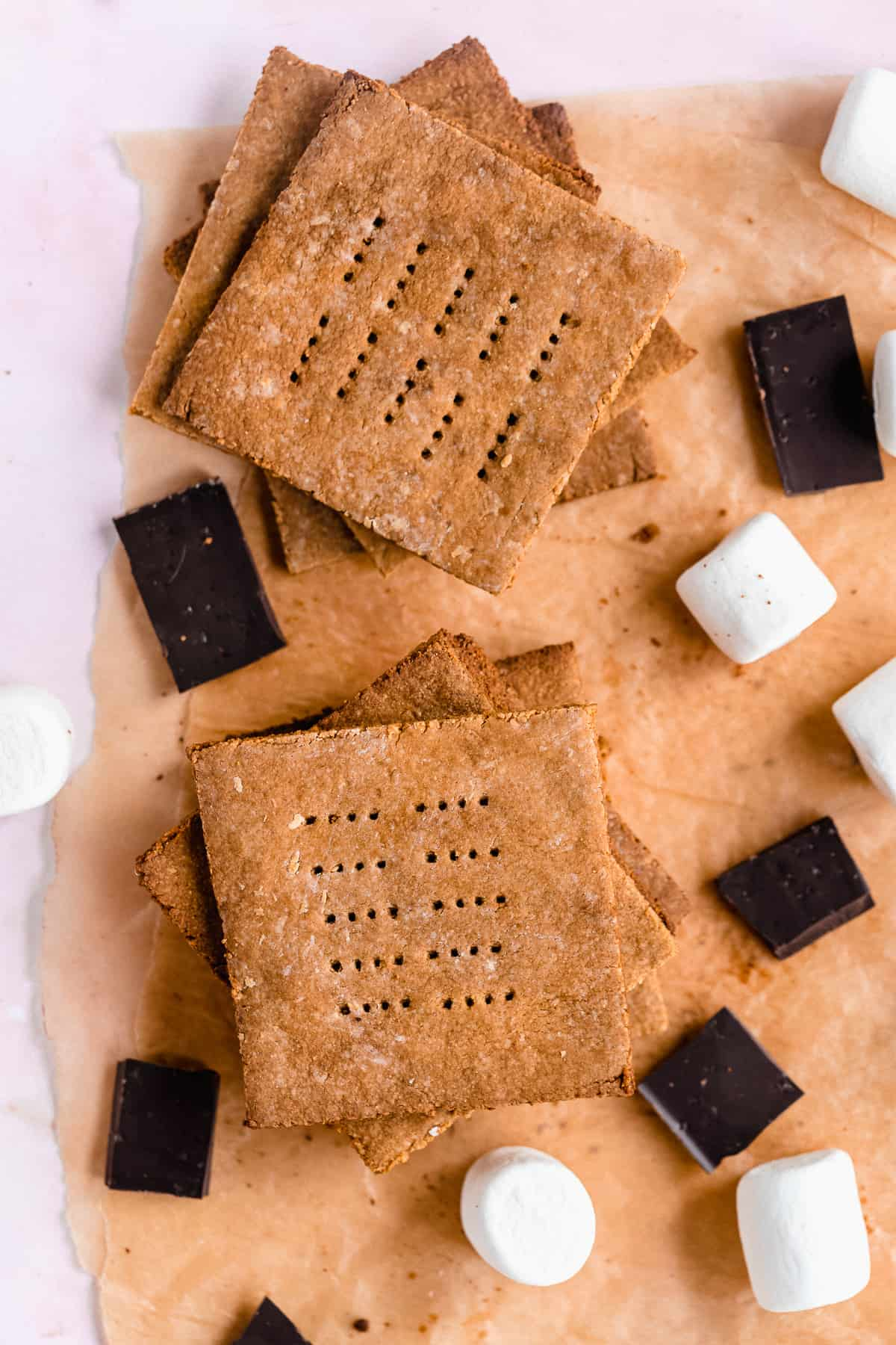 Close up photo of Homemade Graham Crackers stacked on top of one another on parchment paper.  Chocolate pieces and marshmallows are scattered around.