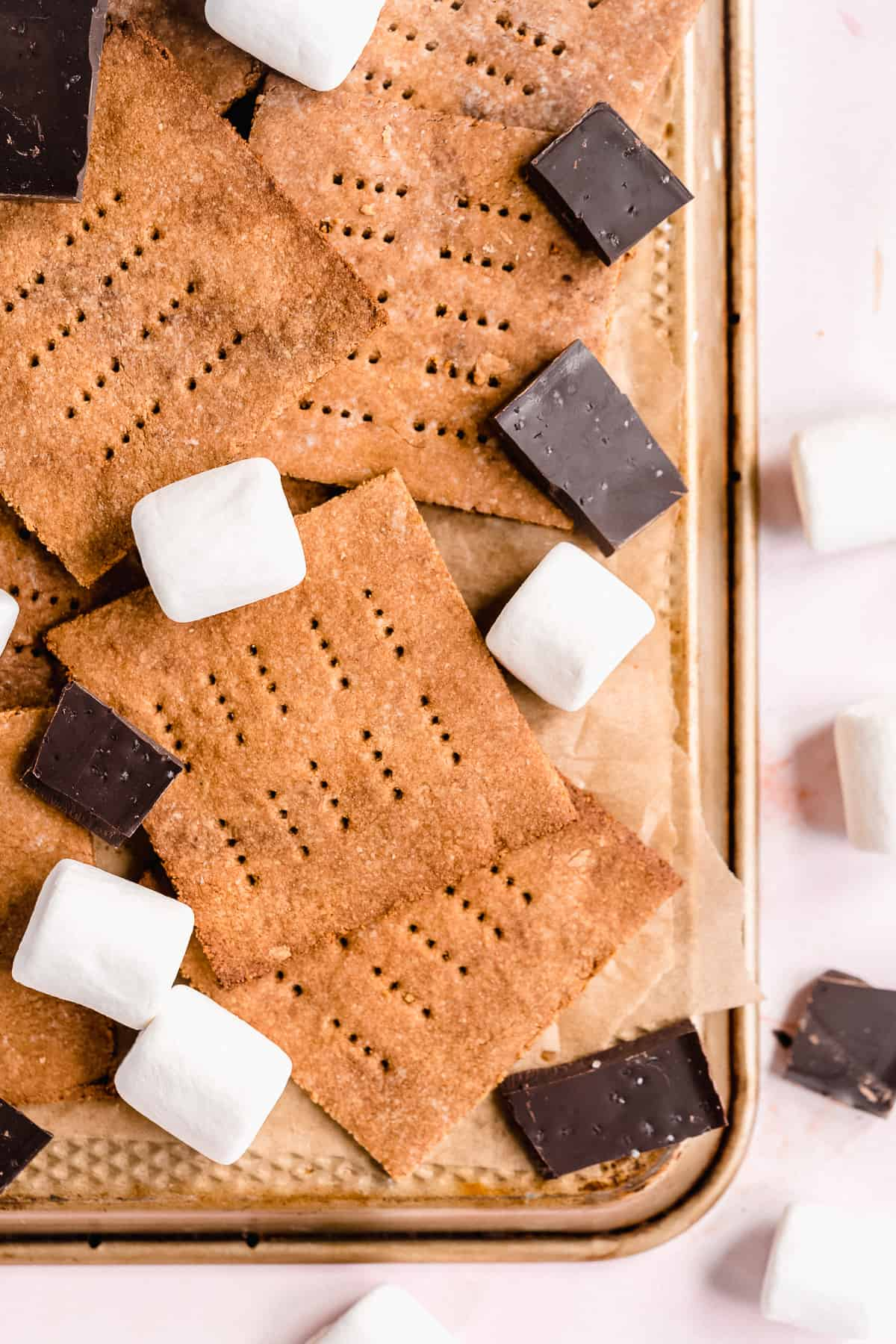Overhead photo of the completed Homemade Graham Crackers arranged on parchment paper on a baking tray.  Chocolate pieces and marshmallow are scattered around.