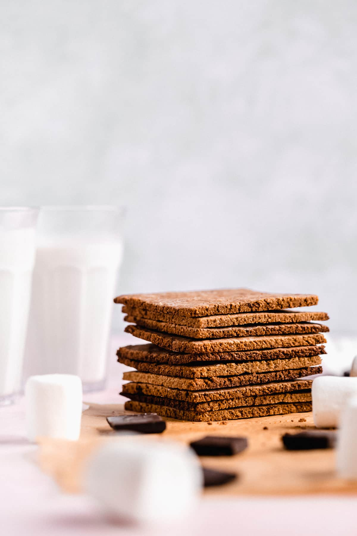Side view of a stack of ten Homemade Graham Crackers on parchment paper.  Two glasses of milk are in the background.  Chocolate pieces and marshmallows are scattered around.