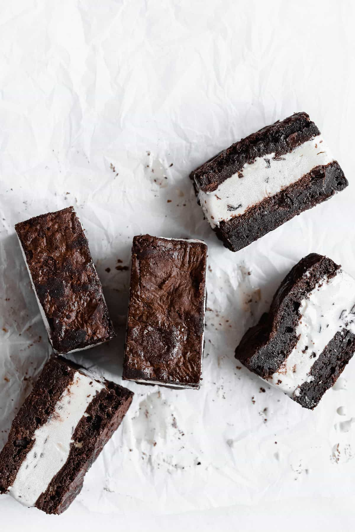 Several Brownie Ice Cream Sandwich squares arranged in white parchment paper.