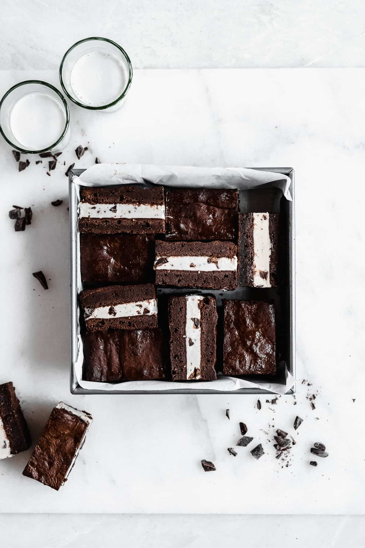 Overhead photo of a square metal baking pan that was used to house the Brownie Ice Cream Sandwiches while they froze.  The Brownie Ice Cream Sandwiches have been cut into squares.