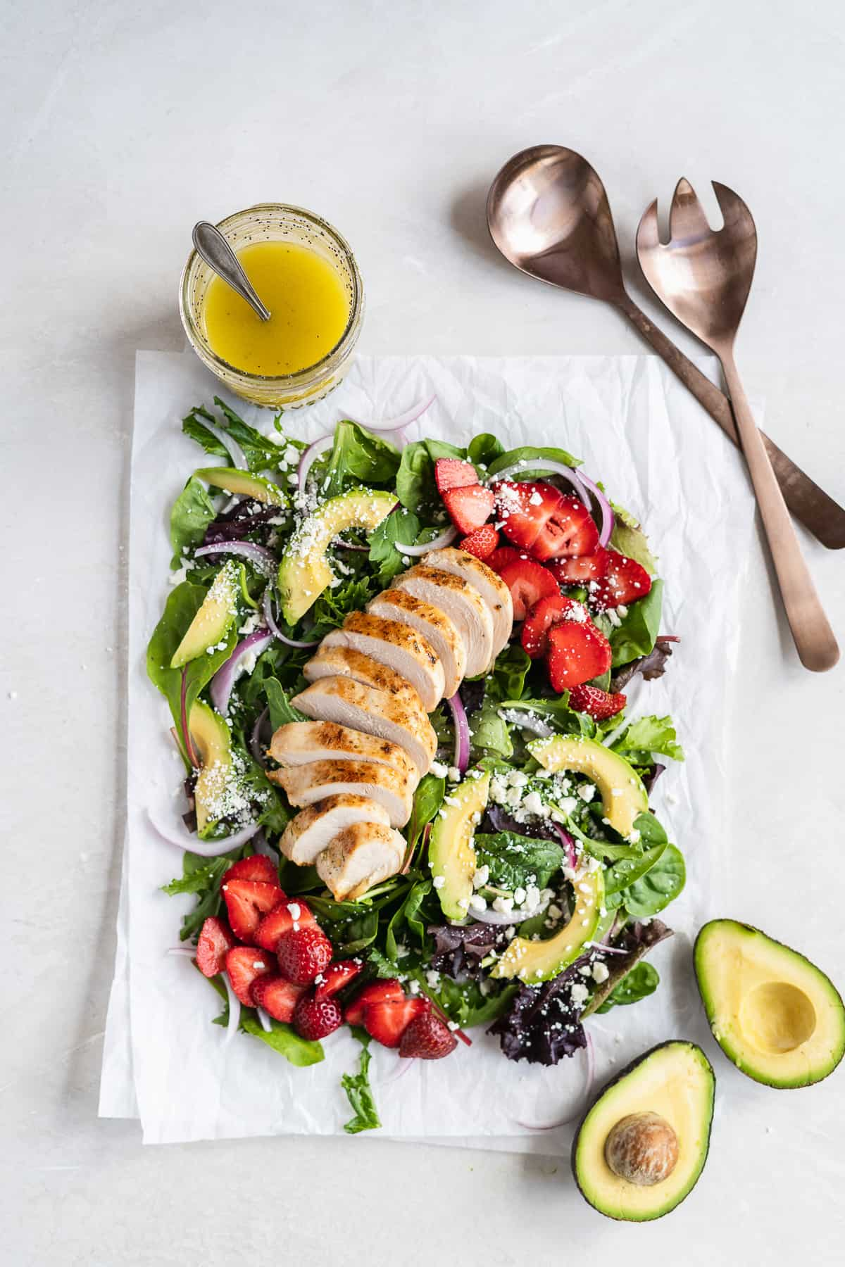 Overhead photo of the Summer Strawberry Goat Cheese Salad with Healthy Poppy Seed Dressing on white parchment paper on a marble slab.  Serving spoons and a jar of dressing are placed nearby.