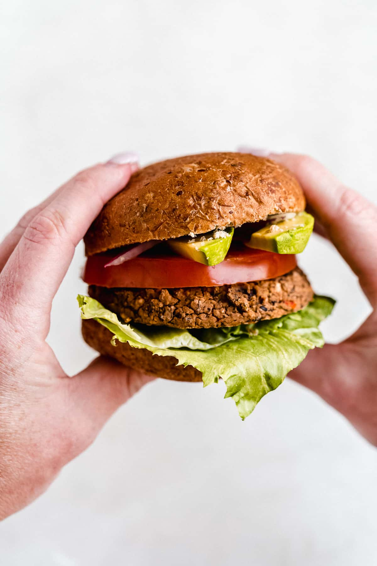 Close up photo of two hands holding a  Black Bean Burger sandwich that is ready to be enjoyed.