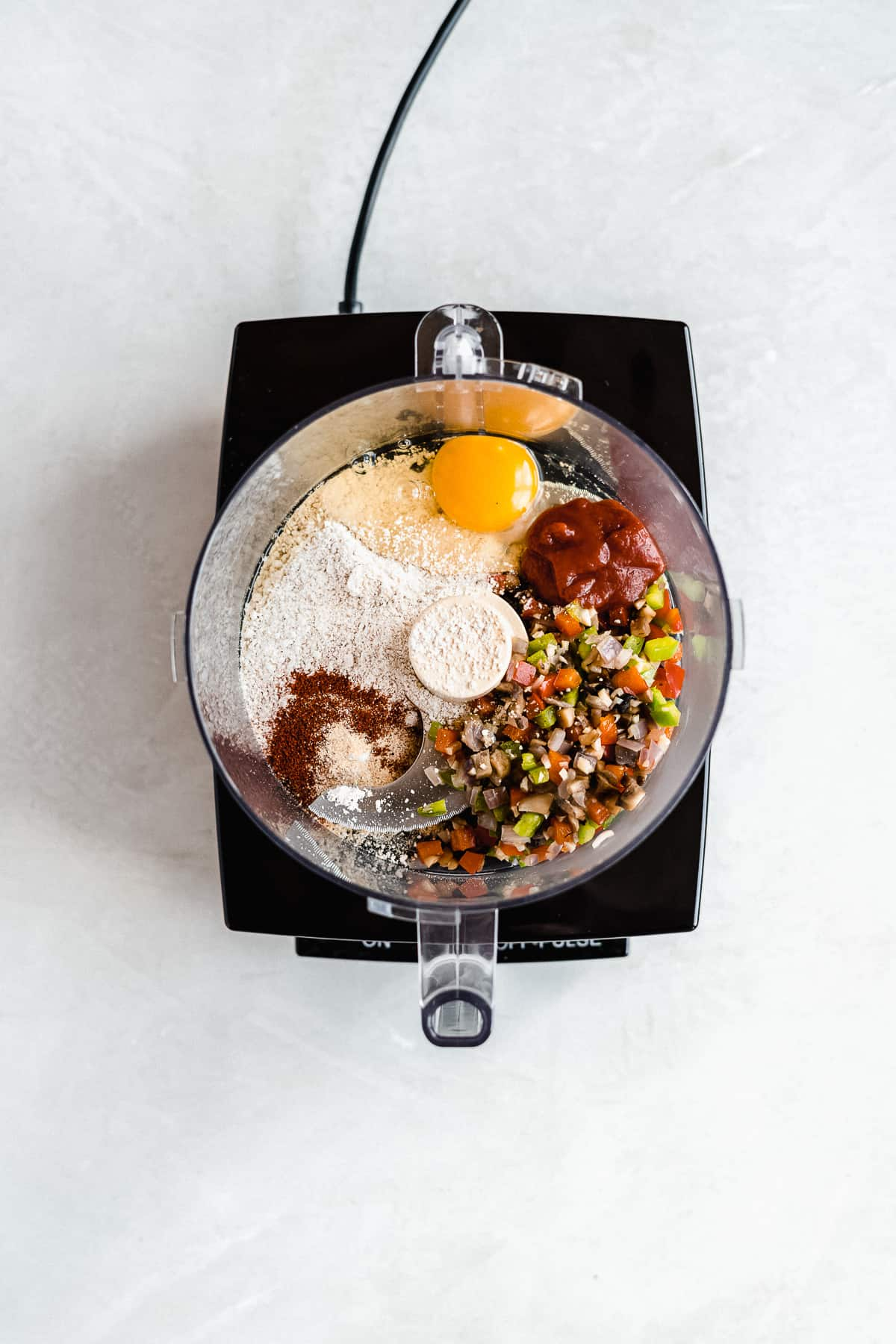 Overhead photo of a mixer with all the ingredients for the black bean burger about to be mixed together.