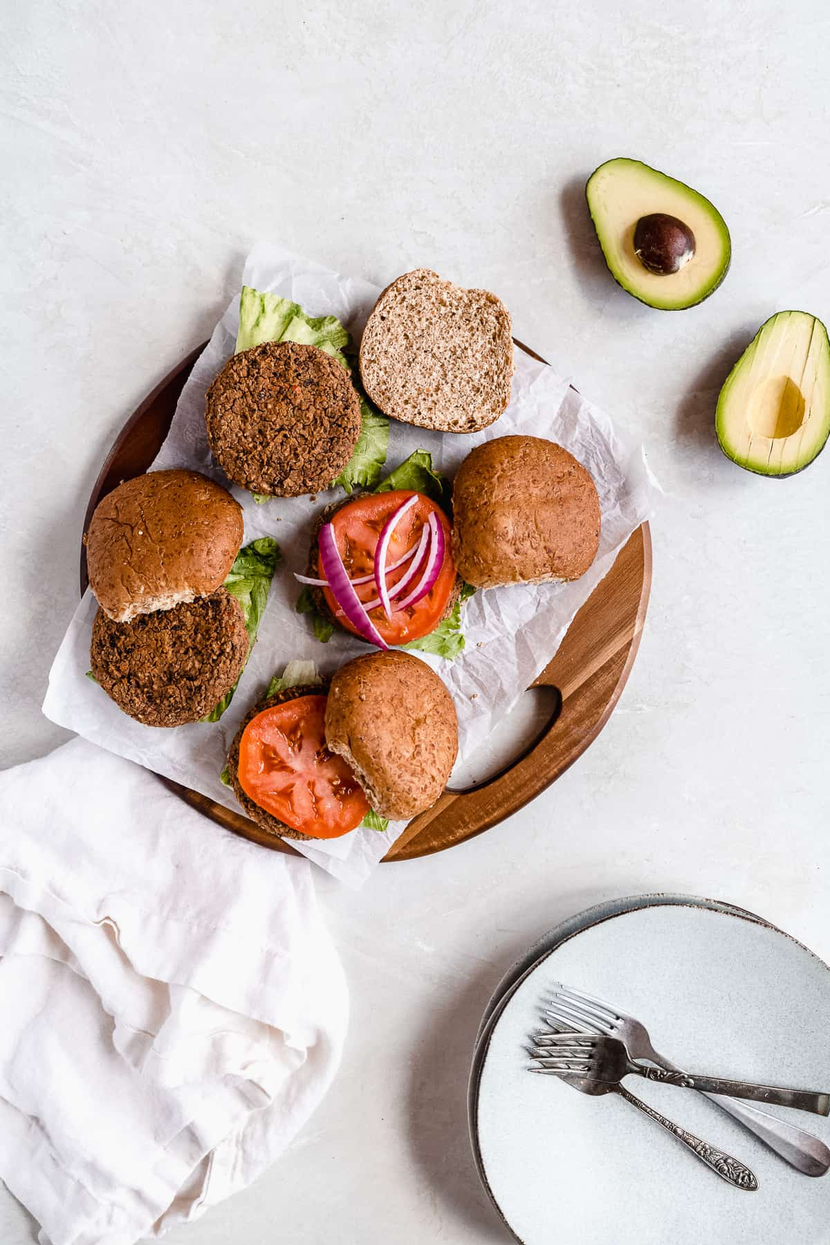 Overhead photo of the buns, tomatoes, avocados and onions arranged on parchment paper on a wooden tray in the process of being built into sandwiches.
