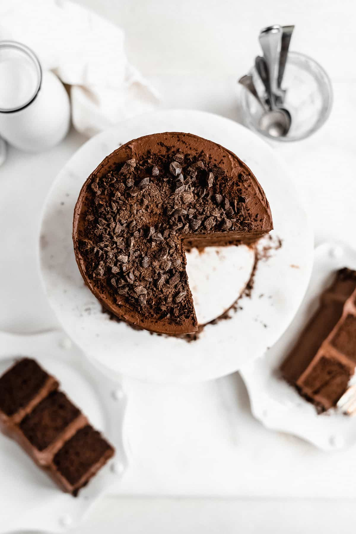 Overhead photo of the top of the Blackout Chocolate Paleo Cake sitting on top of a white marble cake plate.  Several pieces have been cut and removed and placed on small white plates in the background.