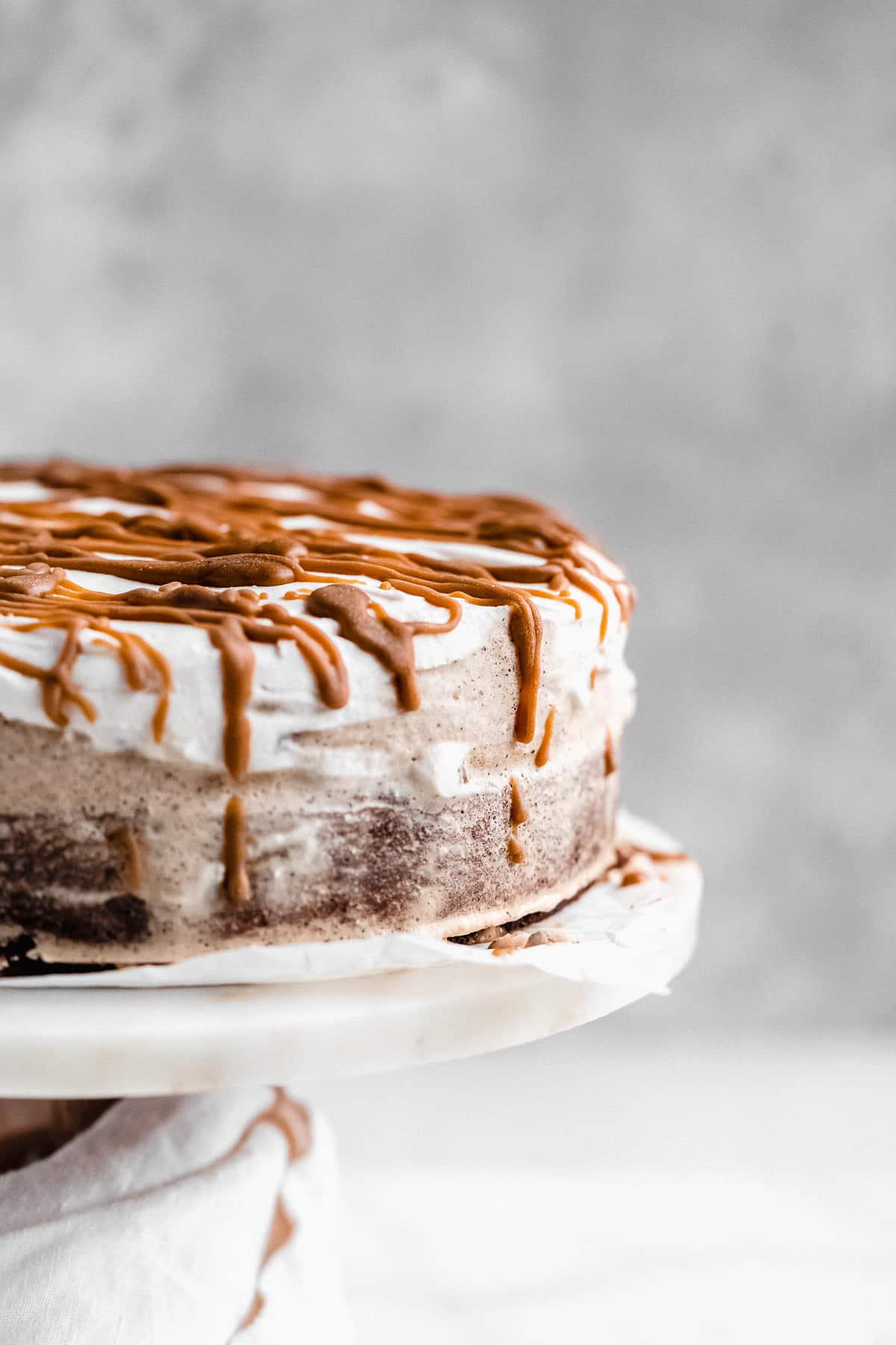 Closeup photo of the side of the Chocolate Espresso Gluten-free Ice Cream Cake sitting on a white marble cake plate.