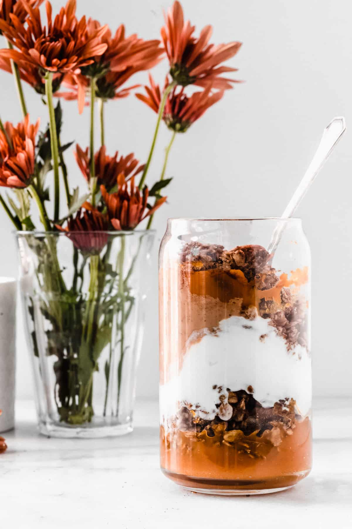 Clear glass sitting on marble surface with pumpkin yogurt parfait and orange flowers in the background.