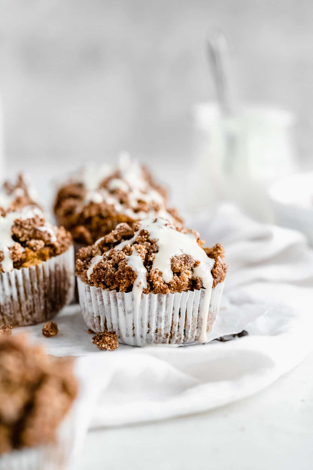 Side view photo of several muffins arranged on white parchment paper ready to be enjoyed.