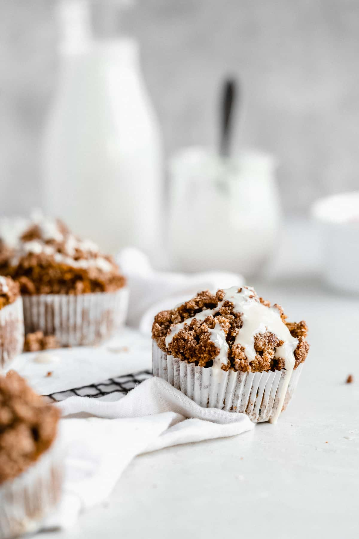 Side view photo of a single Gluten-free Zucchini Muffin with Sweet Maple Cream Cheese Glaze sitting on a cooling rack and white linen cloth.  Several other muffins can be seen in the background.