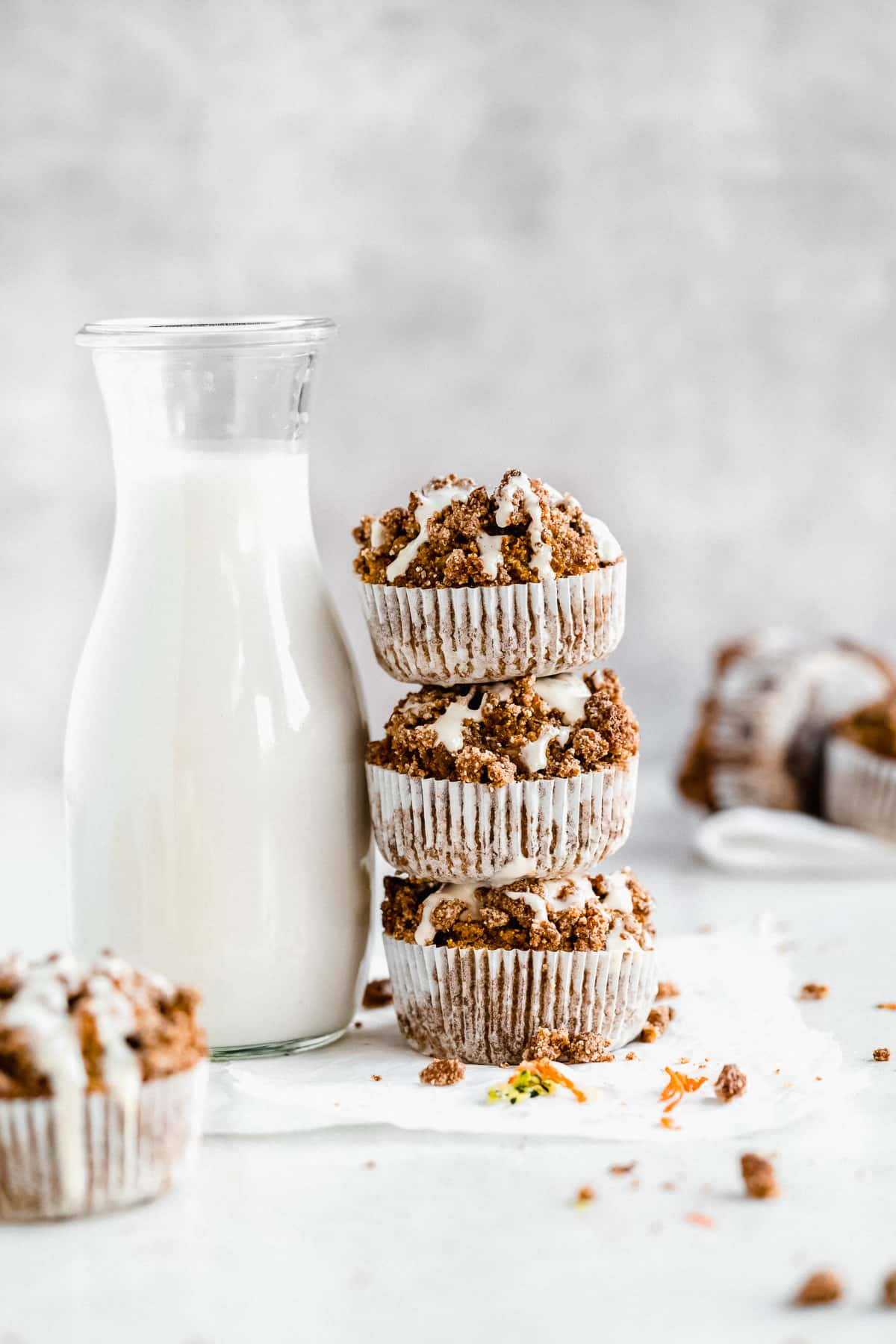 Three Gluten-free Zucchini Muffins with Sweet Maple Cream Cheese Glaze stacked on top of one another next to a carafe of milk.  Additional muffins can be seen in the background.