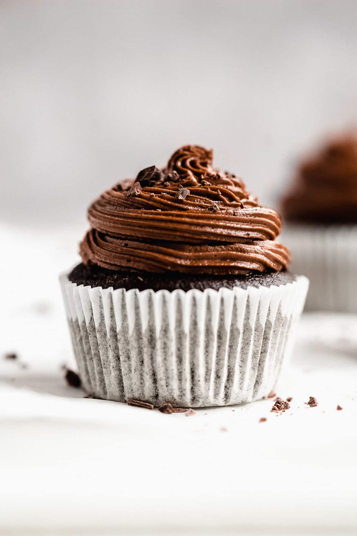 Close up side view photo of a single Gluten-free Chocolate Cupcake sitting on white parchment paper.