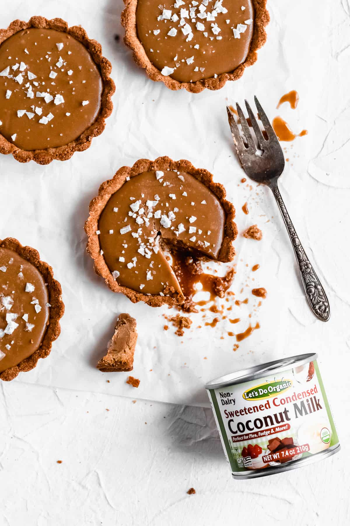 Overhead photo of several completed Vegan Salted Caramel Tarts arranged on white parchment paper.  One tart has a bite missing and a silver fork placed nearby.  A can of Edward & Sons Coconut Milk lays at the bottom of the photo.