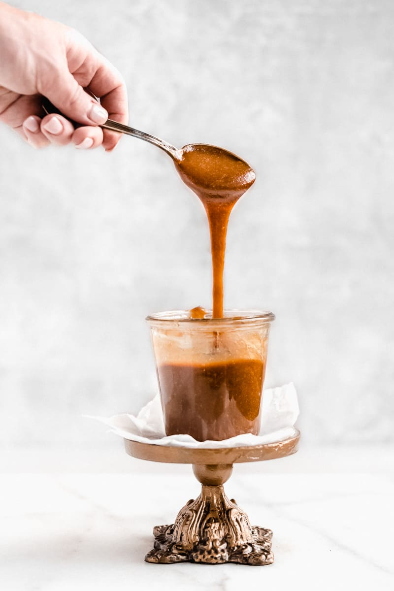 Side view photo of a jar of the 3-Ingredient Vegan Caramel Sauce sitting on a small cake plate.  A hand above is holding a spoon full of the caramel sauce that is dripping into the jar below.