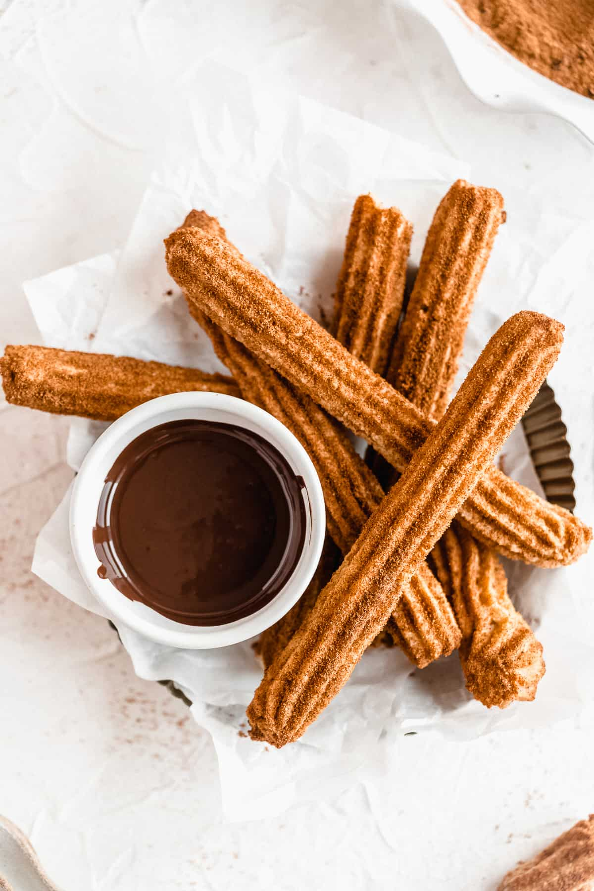 Basket of churros on a white surface with a bowl of melted chocolate.