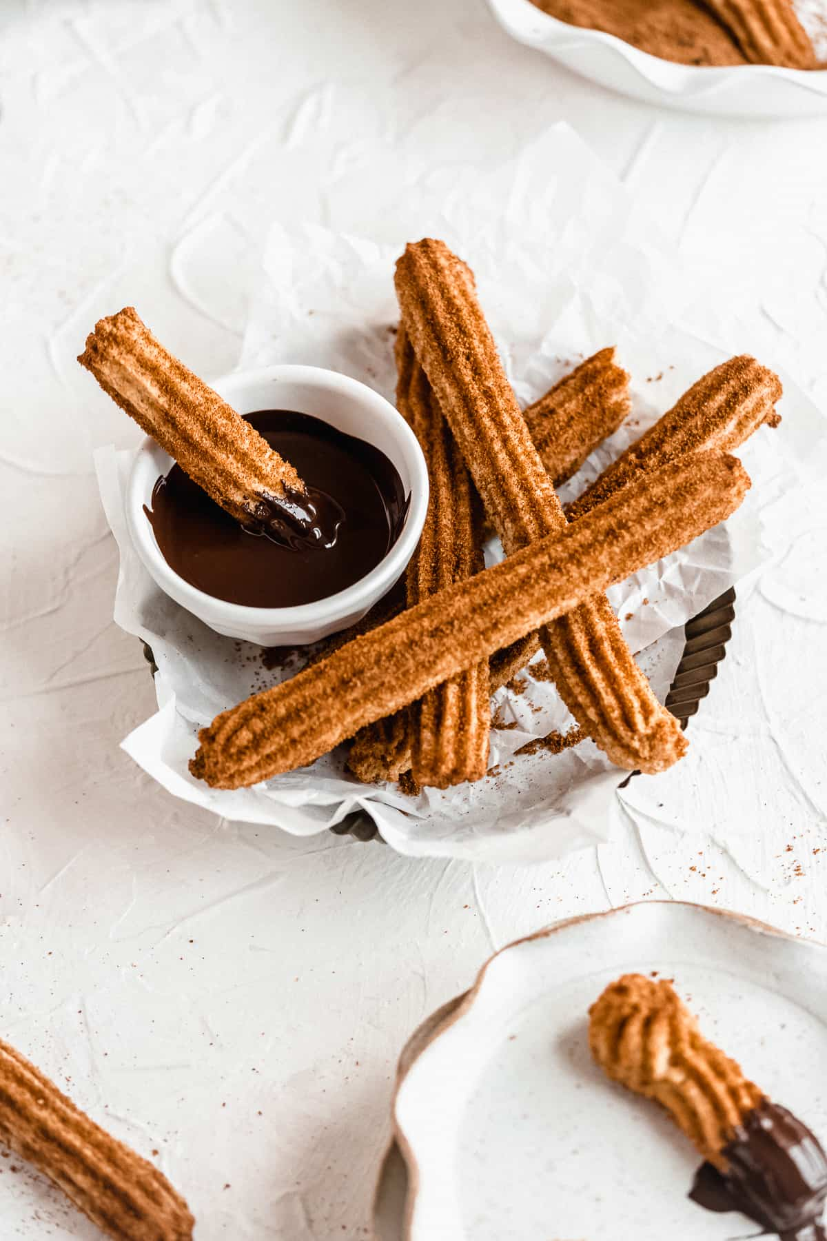 Basket of gluten free churros with one dipped in chocolate.