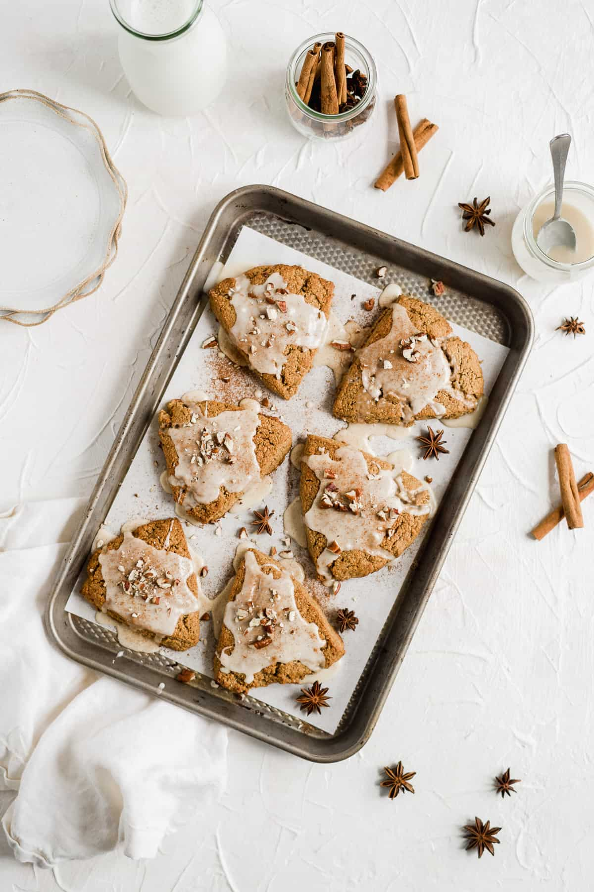 Overhead photo of a baking sheet with parchment paper and six freshly baked and glazed Chai Spiced Gluten-free Vegan Scones.  Some milk, a jar of glaze and several small plates are sitting nearby.