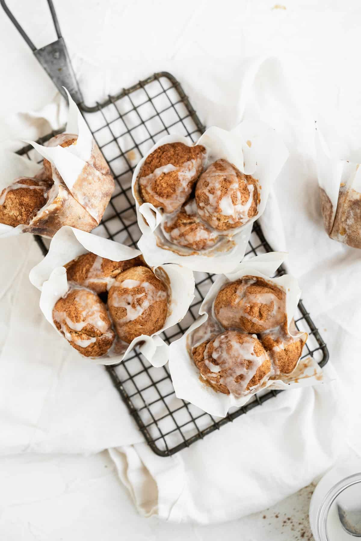 Muffins with white paper liners scattered on a cooling rack with glaze.