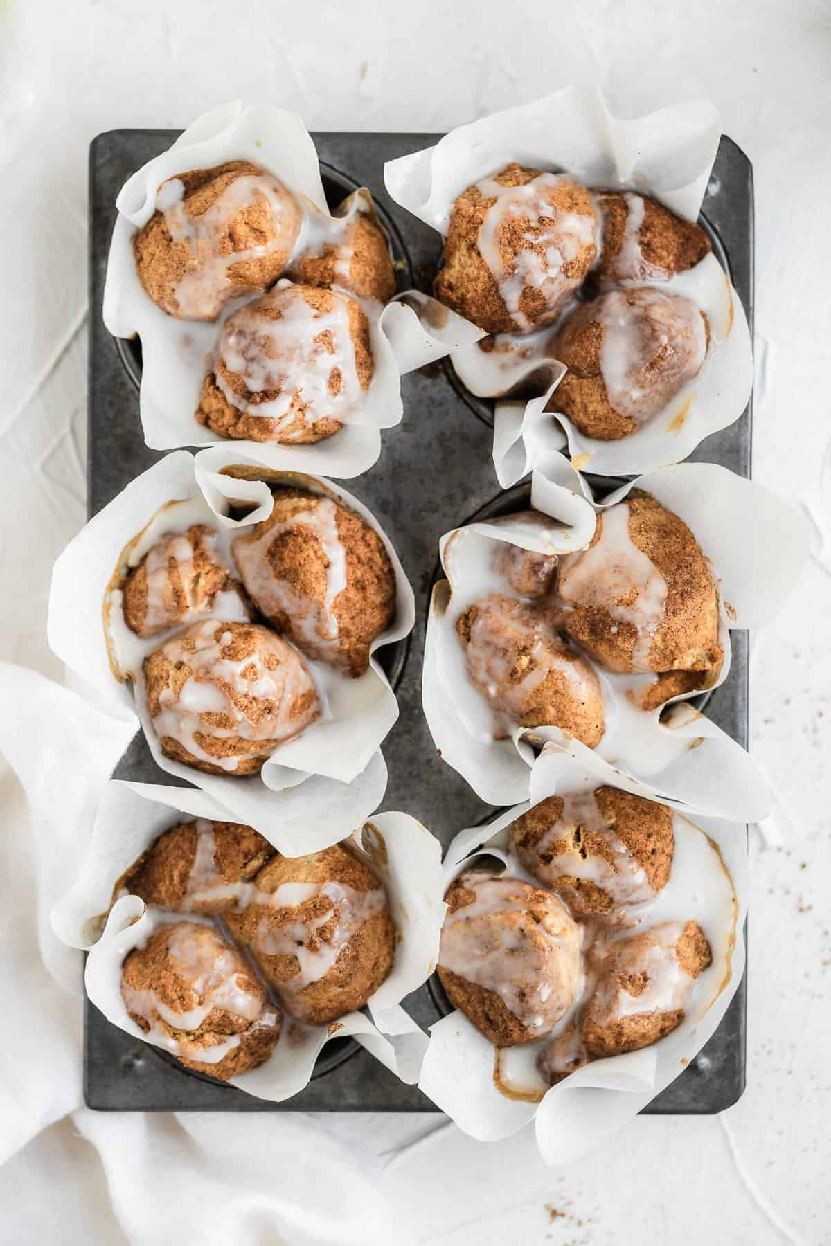 Six muffins in a grey tin with white paper liners and a white glaze.
