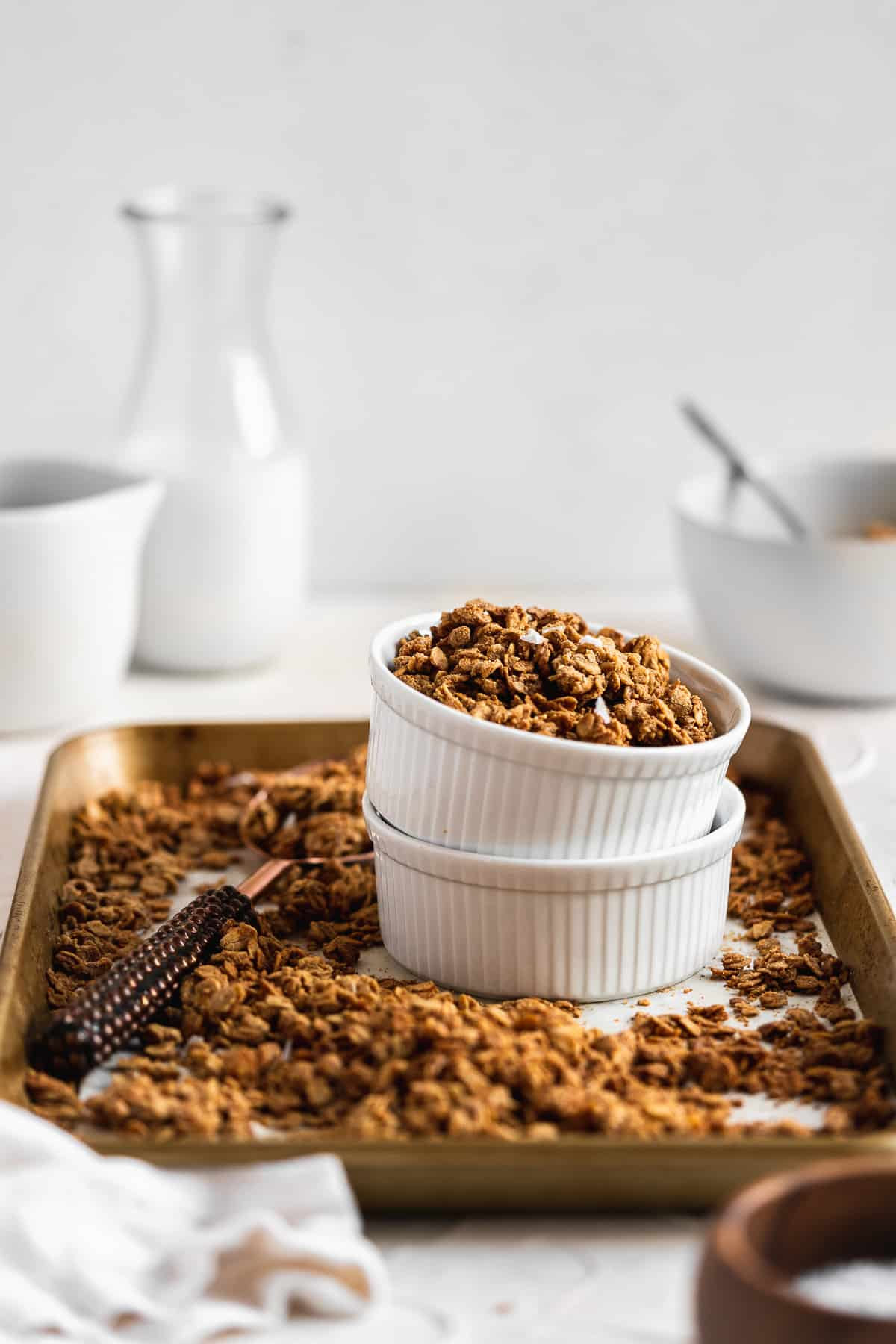 Side view photo of a baking sheet filled with Maple Sea Salt Nut-free Granola.  Two ramekins are stacked and sitting in the middle of the baking sheet.  A serving spoon has filled the ramekin with granola and sits nearby.  A glass of milk is in the background.