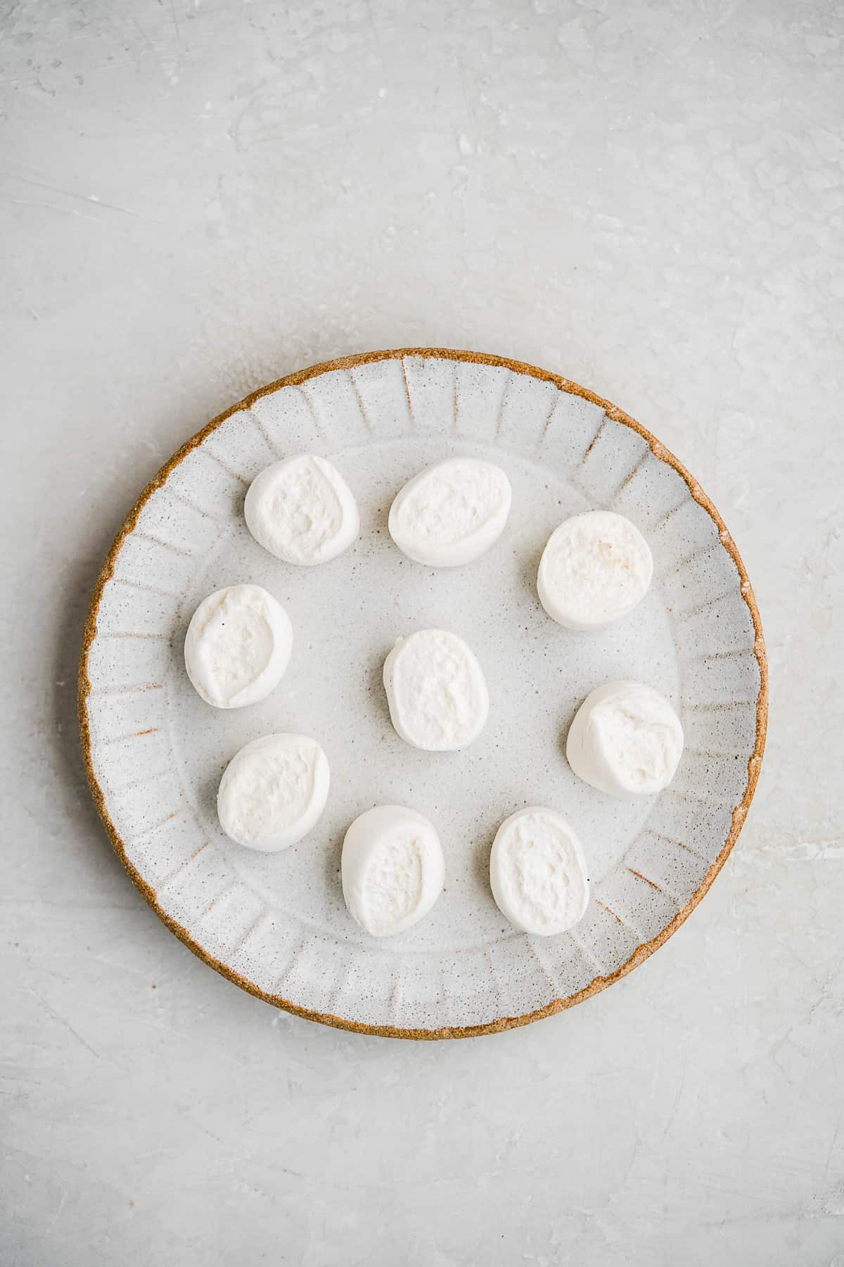 Marshmallows spread out on a plate on a white surface.