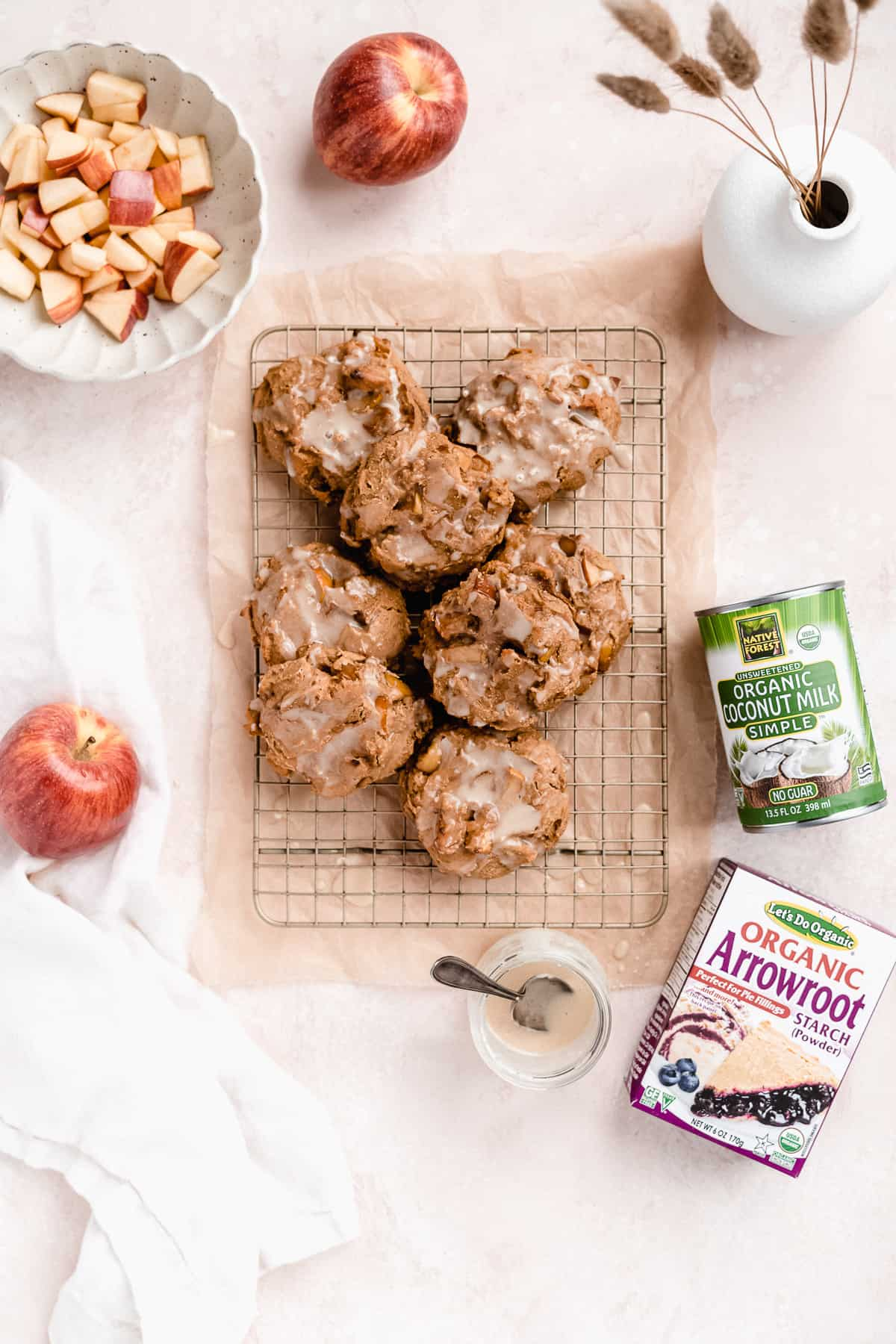 Overhead photo of Vegan Baked Apple Fritters with Maple Coconut Butter Glaze stacked into a mound sitting on top of a metal cooling rack.  A can of Organic Coconut Milk and box of Organic Arrowroot Starch are placed nearby together with several whole apples and a small bowl of apple chunks.