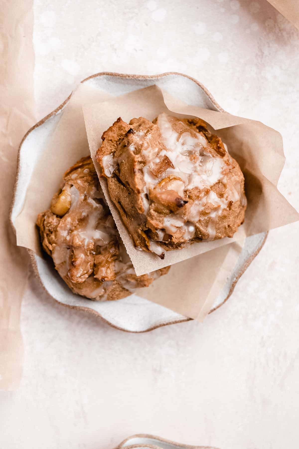 Close up photo of two freshly baked Vegan Baked Apple Fritters with Maple Coconut Butter Glaze each sitting on small parchment paper squares on top of a scalloped plate.