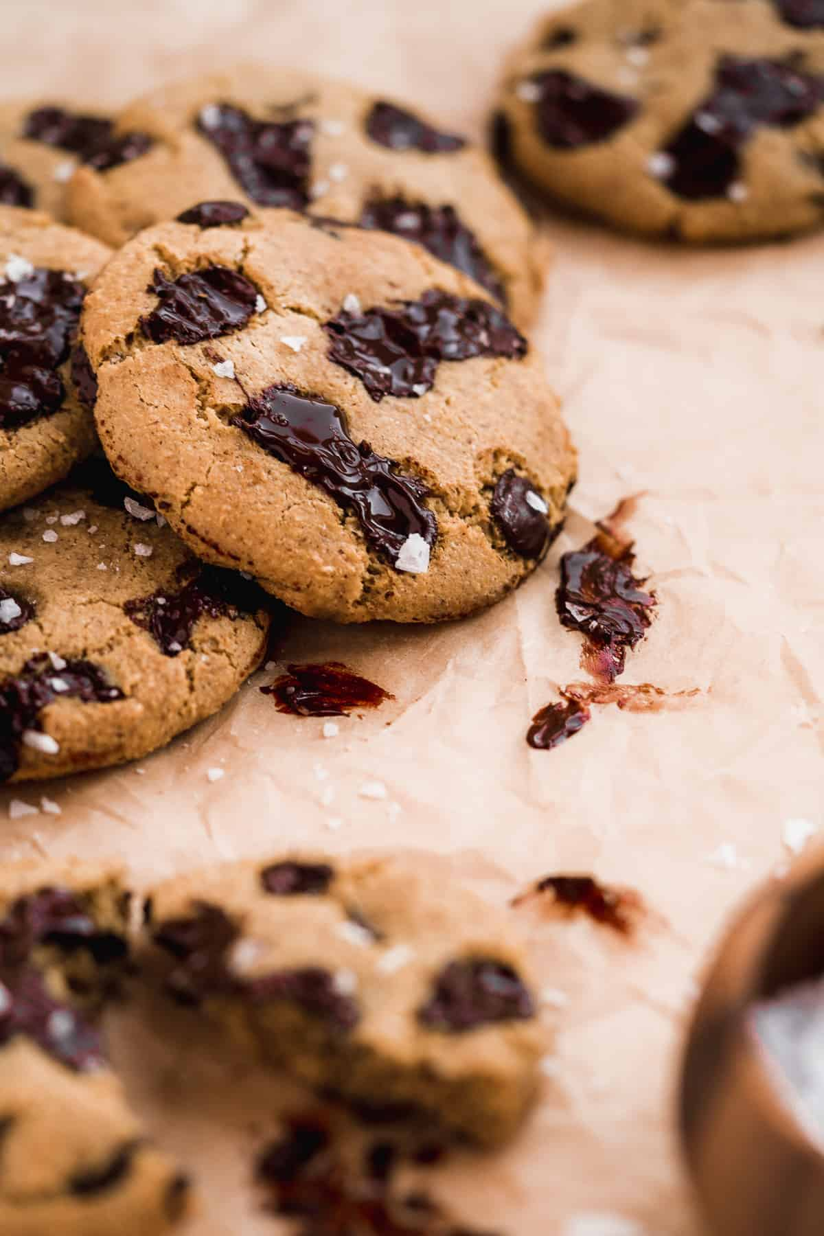Several Almond Butter Chocolate Chip Cookies are mounded on top of one another on parchment paper.  Chocolate chips are gooey and look delicious.