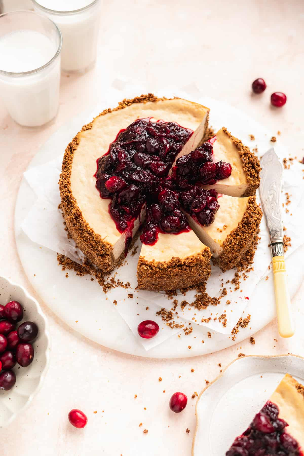 Overhead photo of Vegan Baked Cranberry Cheesecake with Graham Cracker Crust with 3 slices cut sitting on a white marble slab.