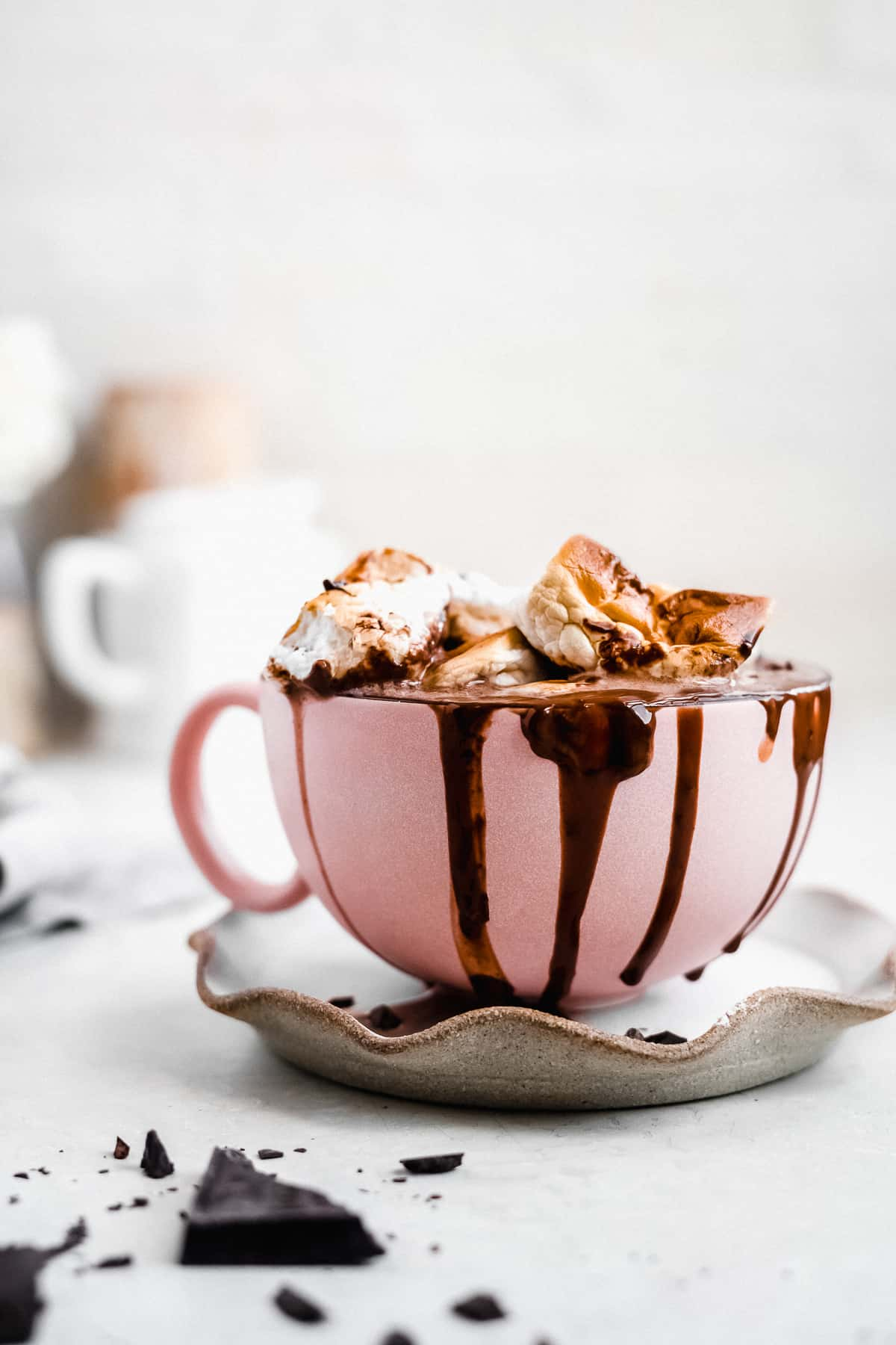 Side view of large pink mug sitting on top of a grey scalloped plate and filled to the brim with Swoon-worthy Dairy-free Hot Chocolate.  Chocolate is running down the sides of the mug.