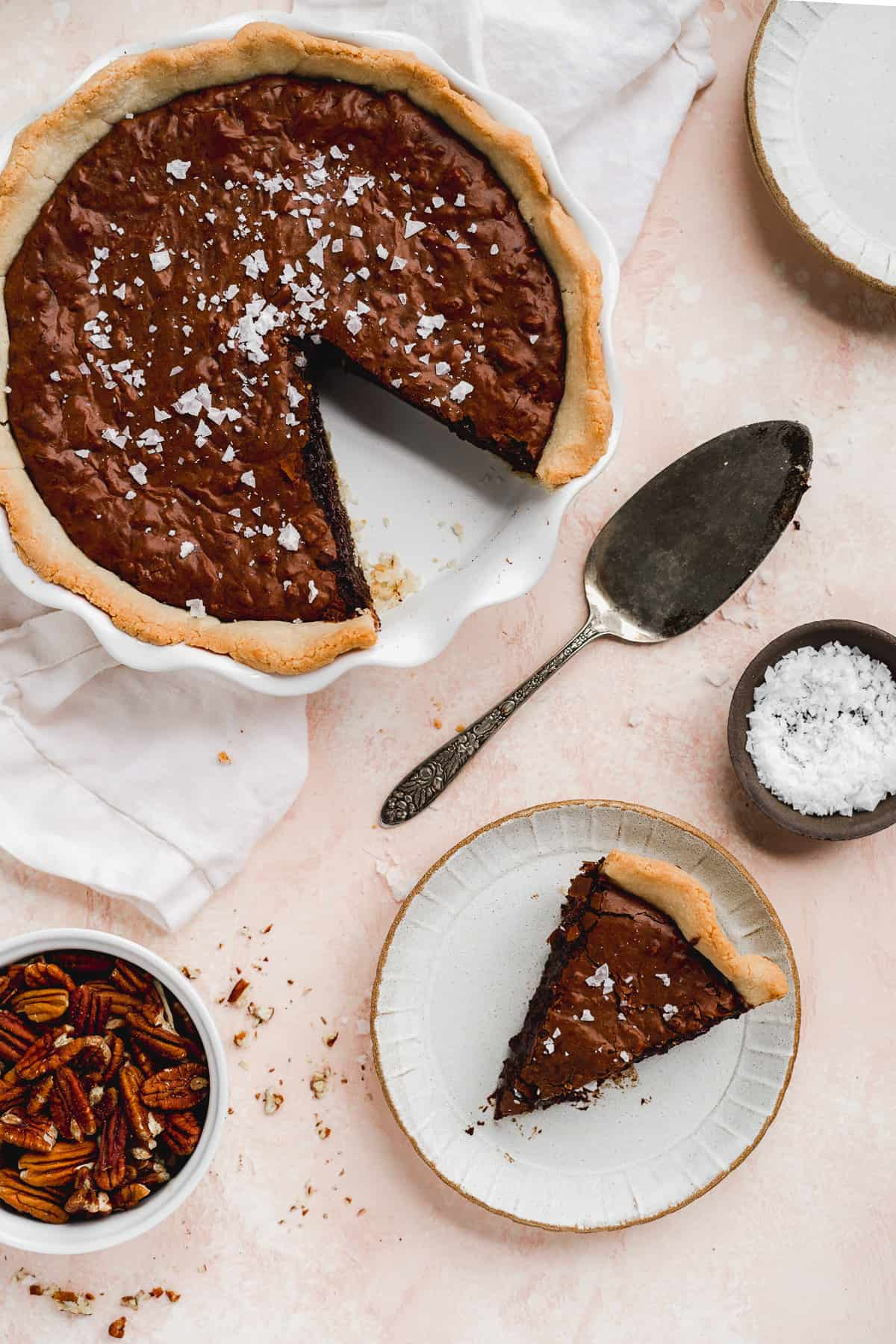 Overhead photo of freshly baked Dark Chocolate Sea Salt Brownie Pecan Pie with one slice missing.  Sliced piece is sitting on a small grey plate nearby.  A pie server is sitting nearby.