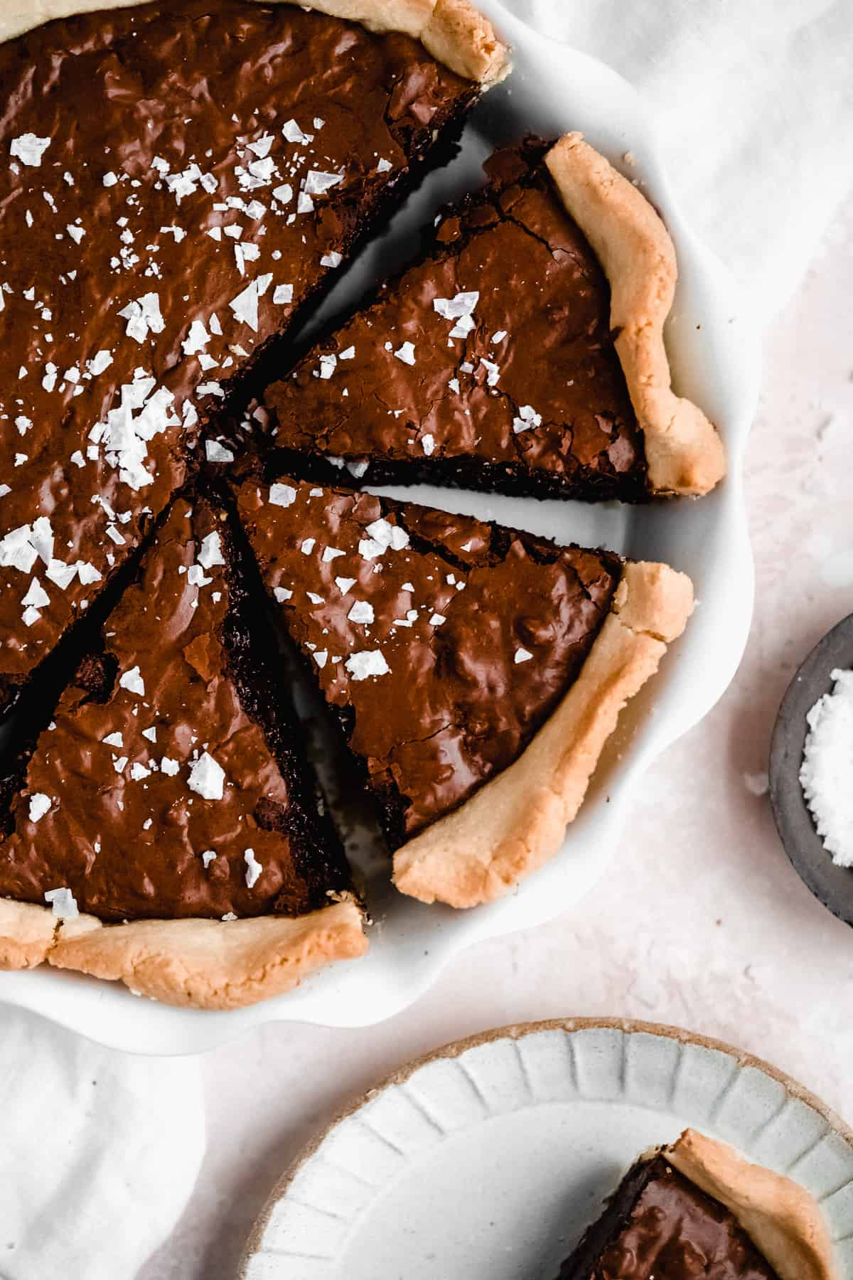 Overhead photo of  freshly baked Dark Chocolate Sea Salt Brownie Pecan Pie in a white scalloped pie pan with 3 pieces cut and separated from the whole.